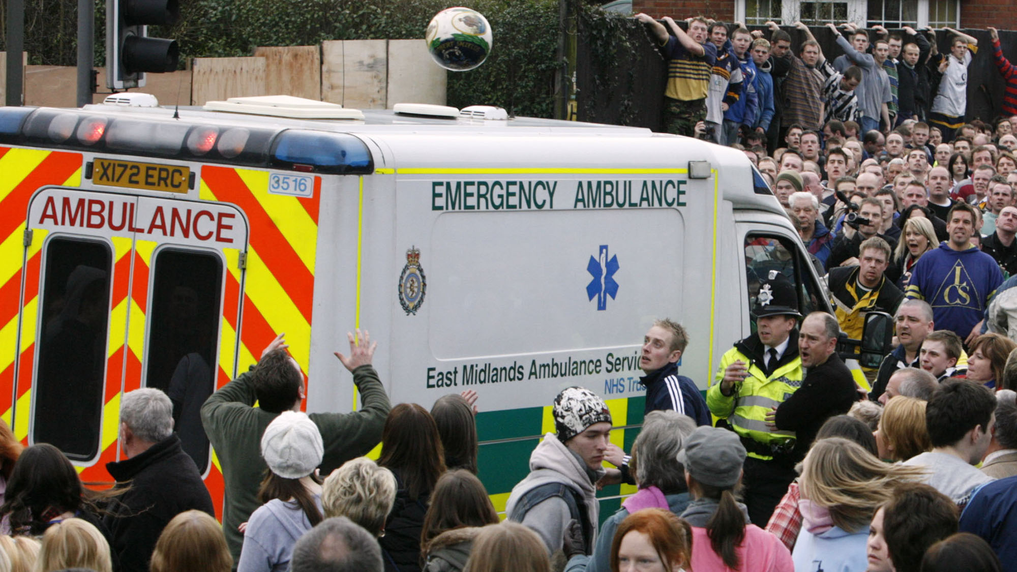 A British police officer throws the ball as an ambulance attempts to pass during the Shrovetide football match in Ashbourne, central England, February 20, 2007. The game dates back to the 17th Century. The aim of the teams, the Up'ards and the Down'ards, is to score by tapping the ball three times on stone goal plinths three miles apart on the banks of the River Henmore.