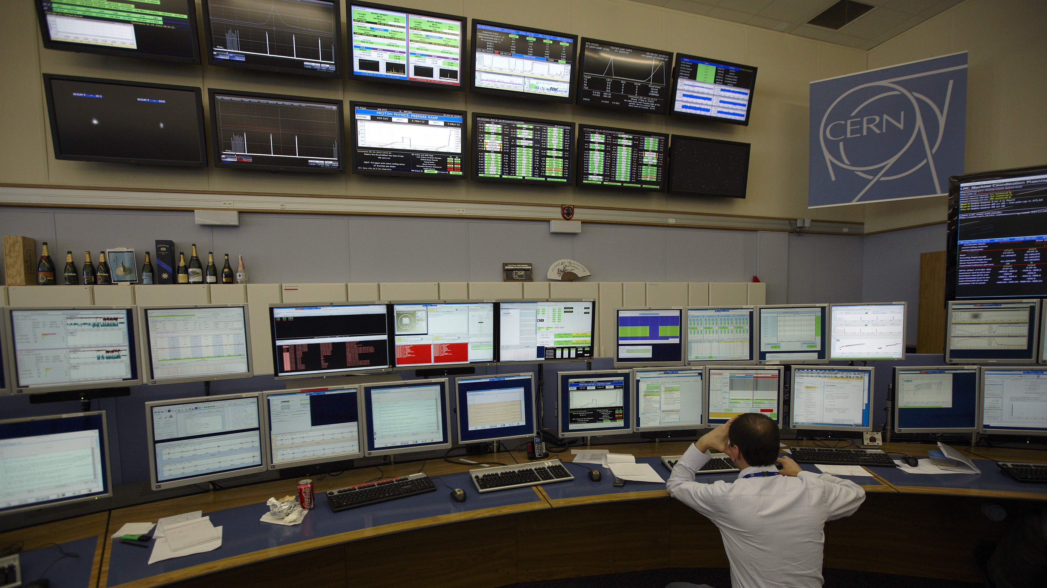 "A technician looks at computer screens during the preparation of the beam in the Control Room of the Large Hadron Collider (LHC) at the European Organisation for Nuclear Research (CERN) near Geneva April 5, 2012. At 0:38 CEST this morning, the LHC shift crew declared ""stable beams"" as two 4 TeV proton beams were brought into collision at the LHC's four interaction points. The collision energy of 8 TeV is a new world record, and increases the machine's discovery potential considerably."