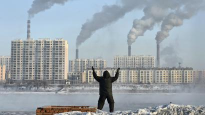 An elderly man exercises in the morning as he faces chimneys emitting smoke behind buildings across the Songhua river in Jilin, Jilin province, February 24, 2013.