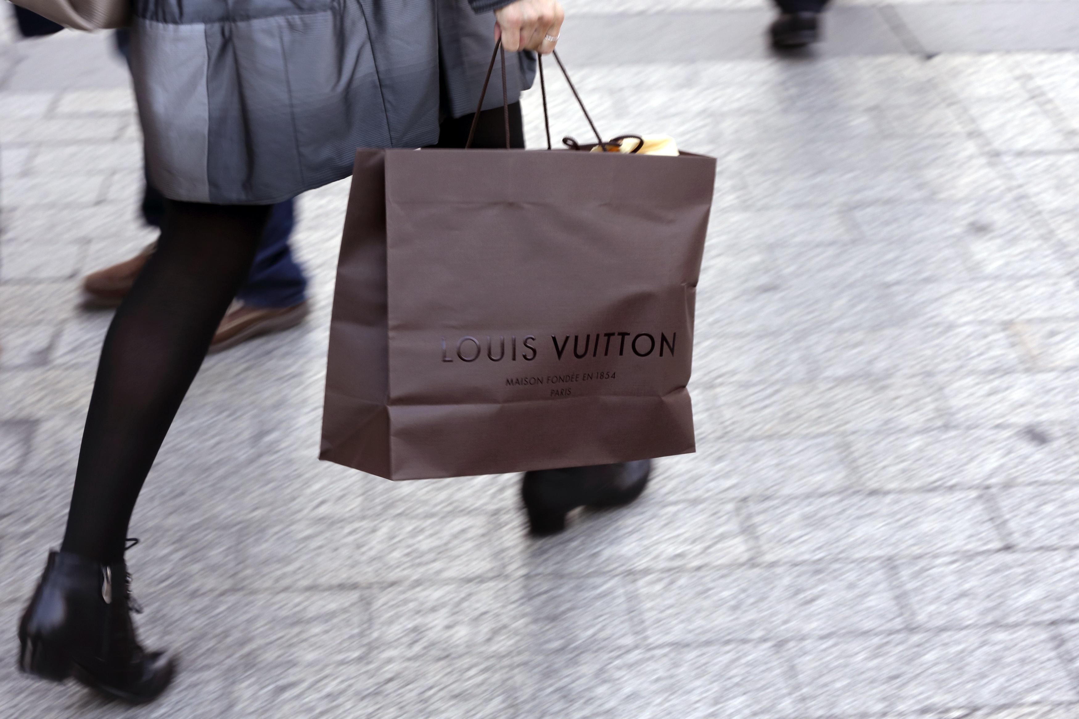 A woman walks with a Louis Vuitton shopping bag as she leaves a Louis Vuitton store in Paris.
