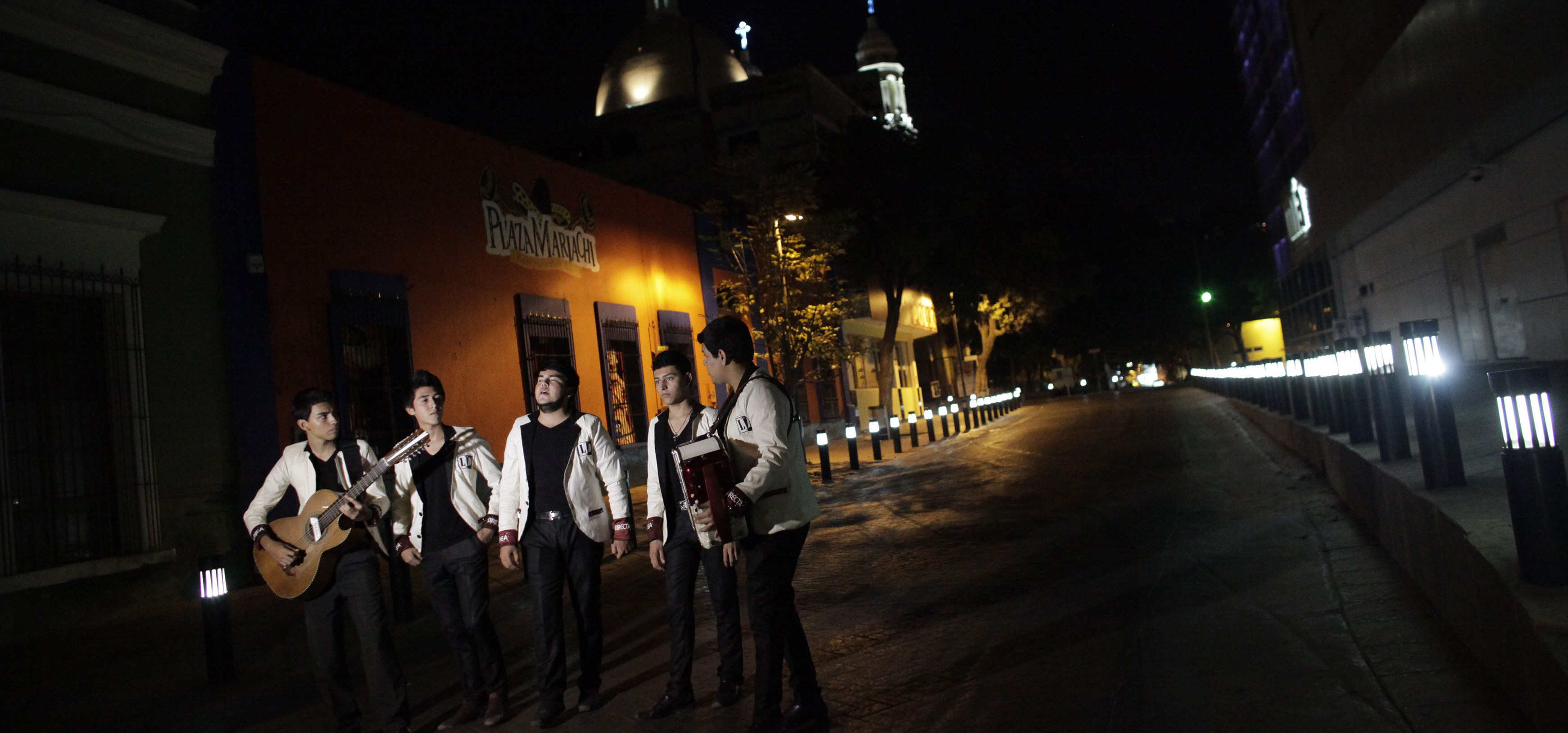 Members of a band record a narcocorrido in downtown Culiaca