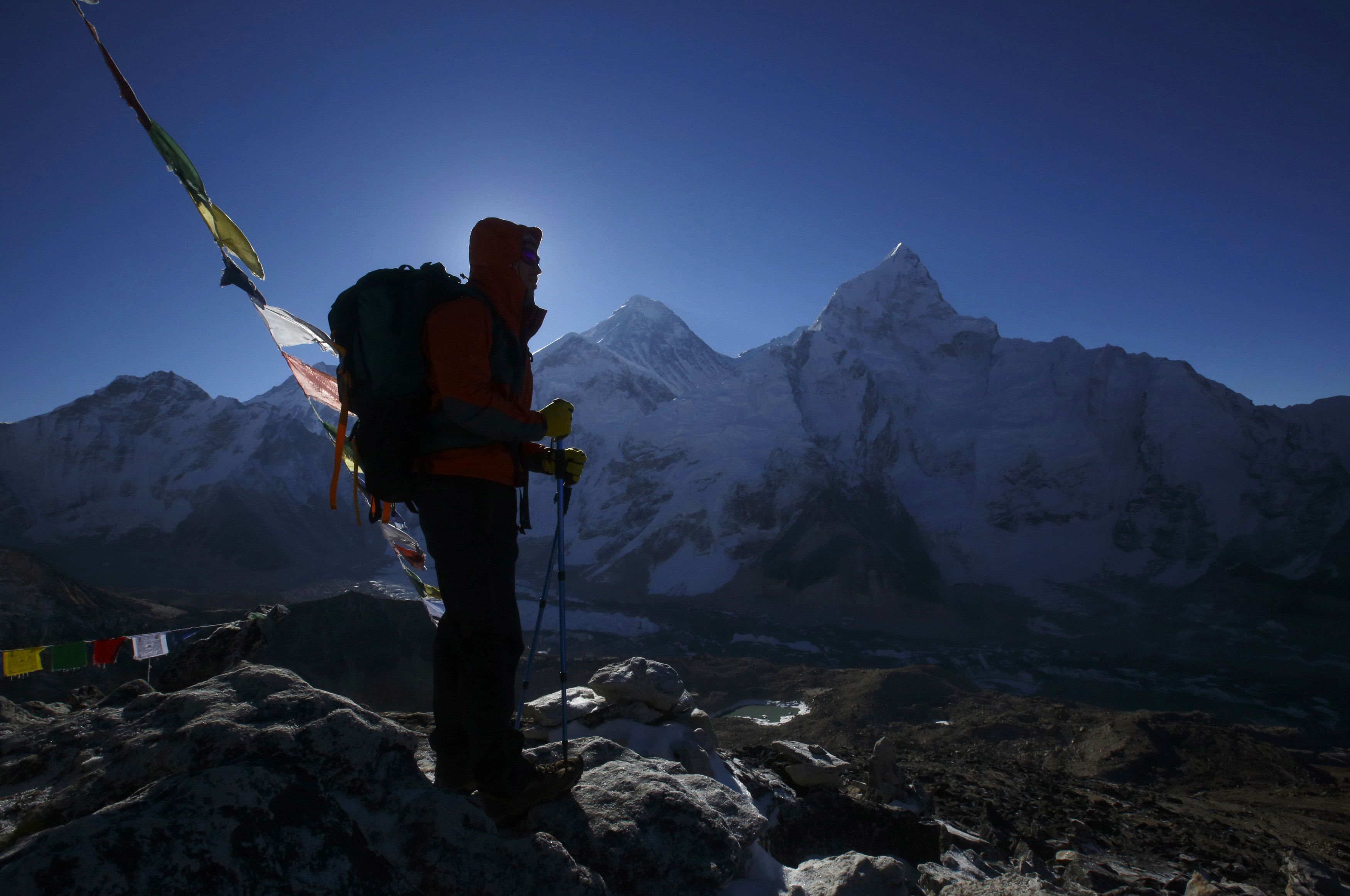 A trekker stands in front of Mount Everest, which is 8,850 meters high (C), at Kala Patthar in Solukhumbu District May 7, 2014. More than 4,000 climbers have reached the summit of Everest, the world's highest peak, since it was first scaled by Sir Edmund Hillary and Tenzing Norgay Sherpa in 1953. In April, an avalanche killed 16 Nepali Sherpa guides who were fixing ropes and ferrying supplies for their foreign clients to climb the 8,850-metre (29,035-foot) peak. The accident - the deadliest in the history of Mount Everest - triggered a dispute between sherpa guides who wanted a climbing ban in honour of their colleagues and the Nepali government that refused to close the mountain. The sherpas staged a boycott, forcing hundreds of foreign climbers to call off their bids to climb Everest.  Picture taken May 7, 2014.  REUTERS/Navesh Chitrakar (NEPAL - Tags: ENVIRONMENT SOCIETY BUSINESS EMPLOYMENT TRAVEL TPX IMAGES OF THE DAY)  ATTENTION EDITORS: PICTURE 44 OF 45 FOR PACKAGE 'AFTER THE AVALANCHE - ASCENT TO EVEREST' TO FIND ALL IMAGES SEARCH 'CHITRAKAR EVEREST' - RTR3SBJM