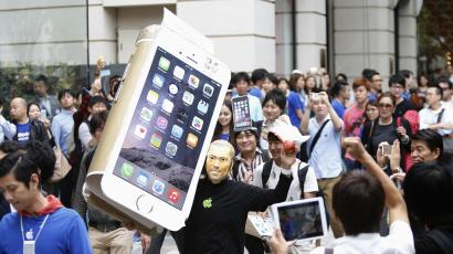 A man wearing a mask depicting Steve Jobs holds up a cardboard cut-out of Apple's new iPhone 6, as he walks into the Apple Store in Tokyo.