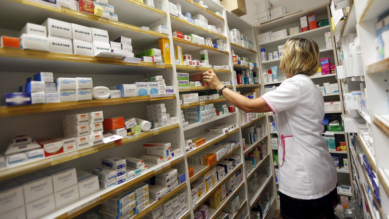 A pharmacist selects drugs inside her pharmacy in Bordeaux, France, September 15, 2015.