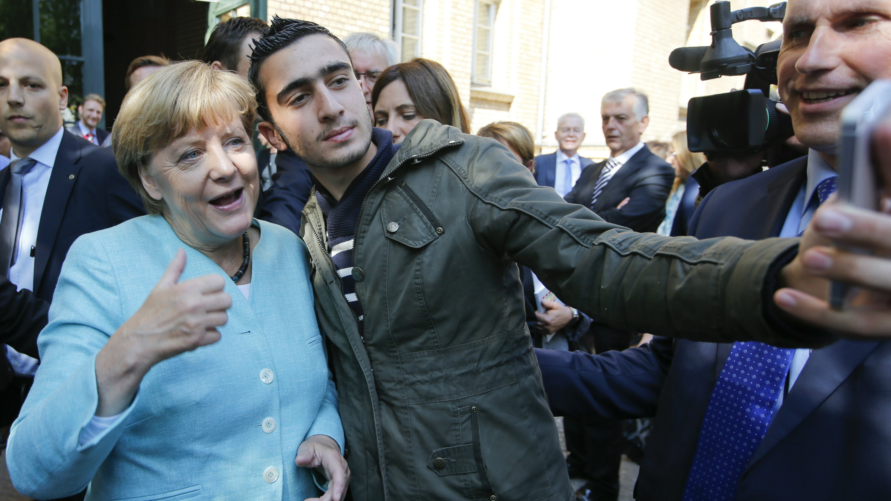 A migrant takes a selfie with German Chancellor Angela Merkel outside a refugee camp near the Federal Office for Migration and Refugees after registration at Berlin's Spandau district, Germany September 10, 2015