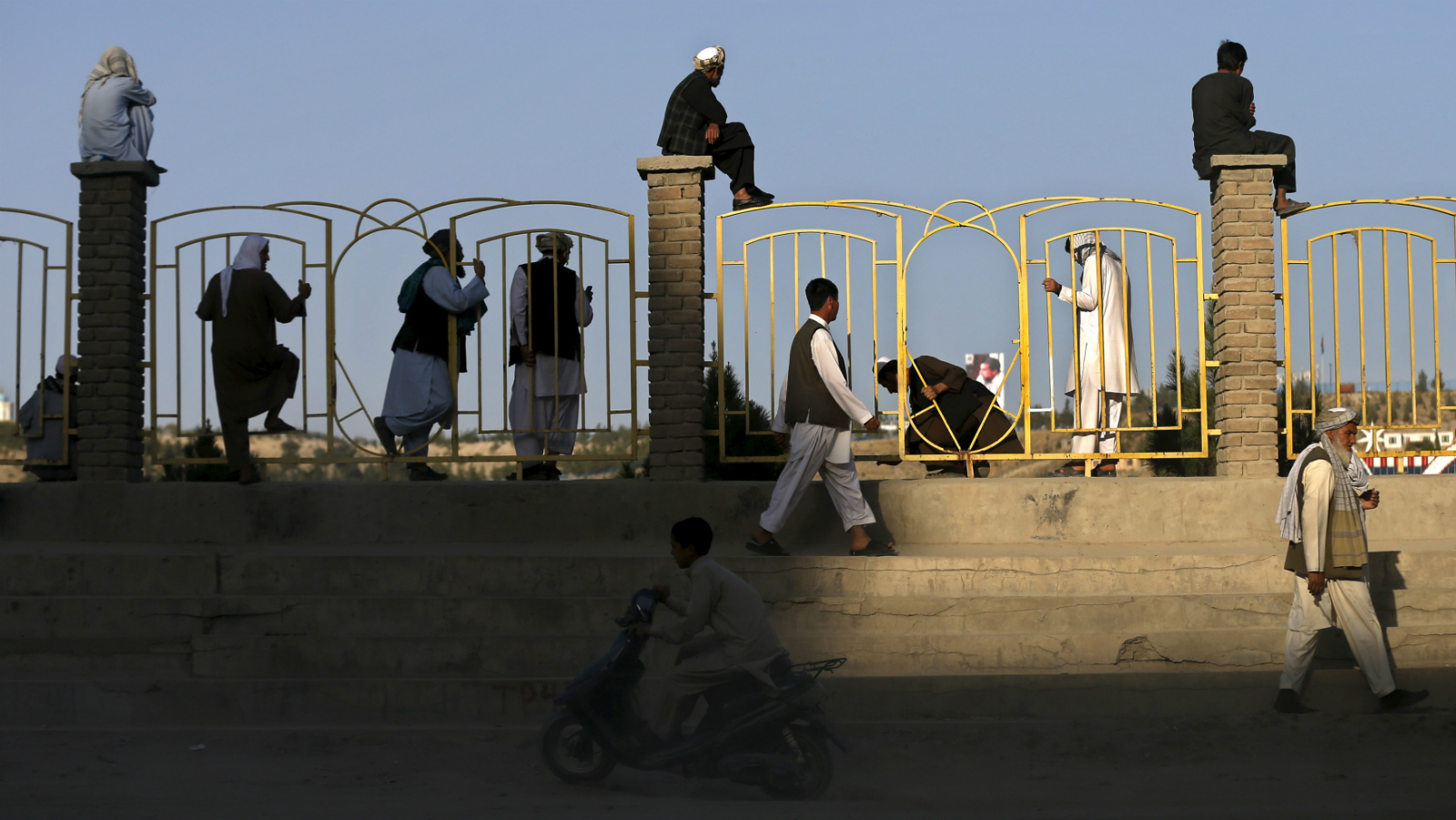 Afghan men sit on a wall as they watch others play football in Kabul, Afghanistan September 11, 2015.