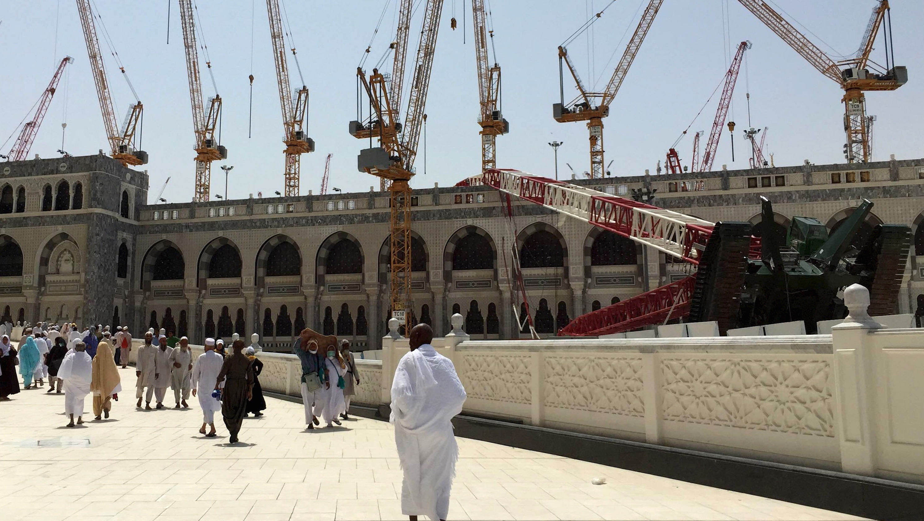Muslim pilgrims walk near a construction crane which crashed in the Grand Mosque in the Muslim holy city of Mecca, Saudi Arabia