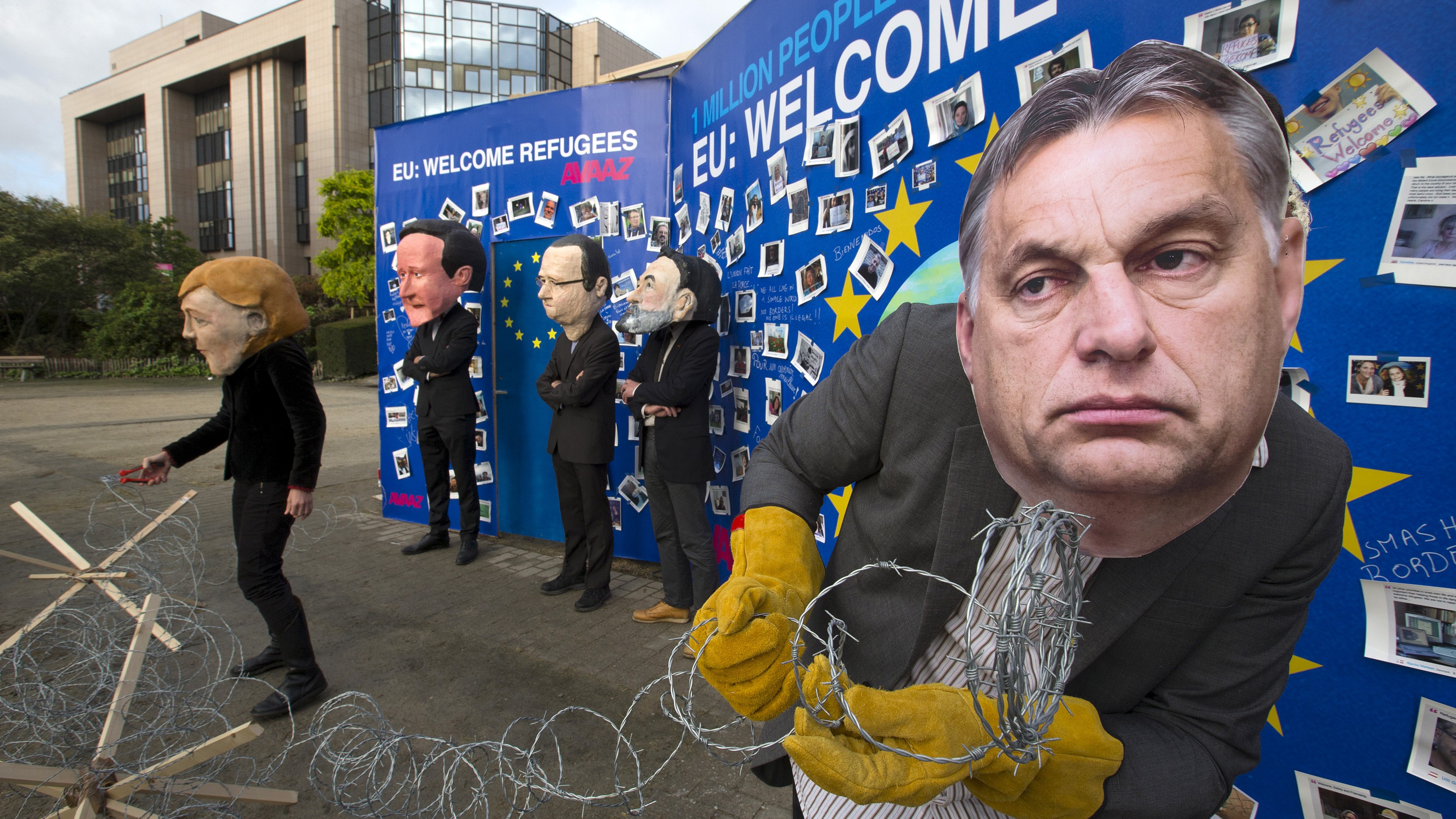 Avaaz's activists wear masks depicting EU leaders during a demonstration in support of migrants in Brussels