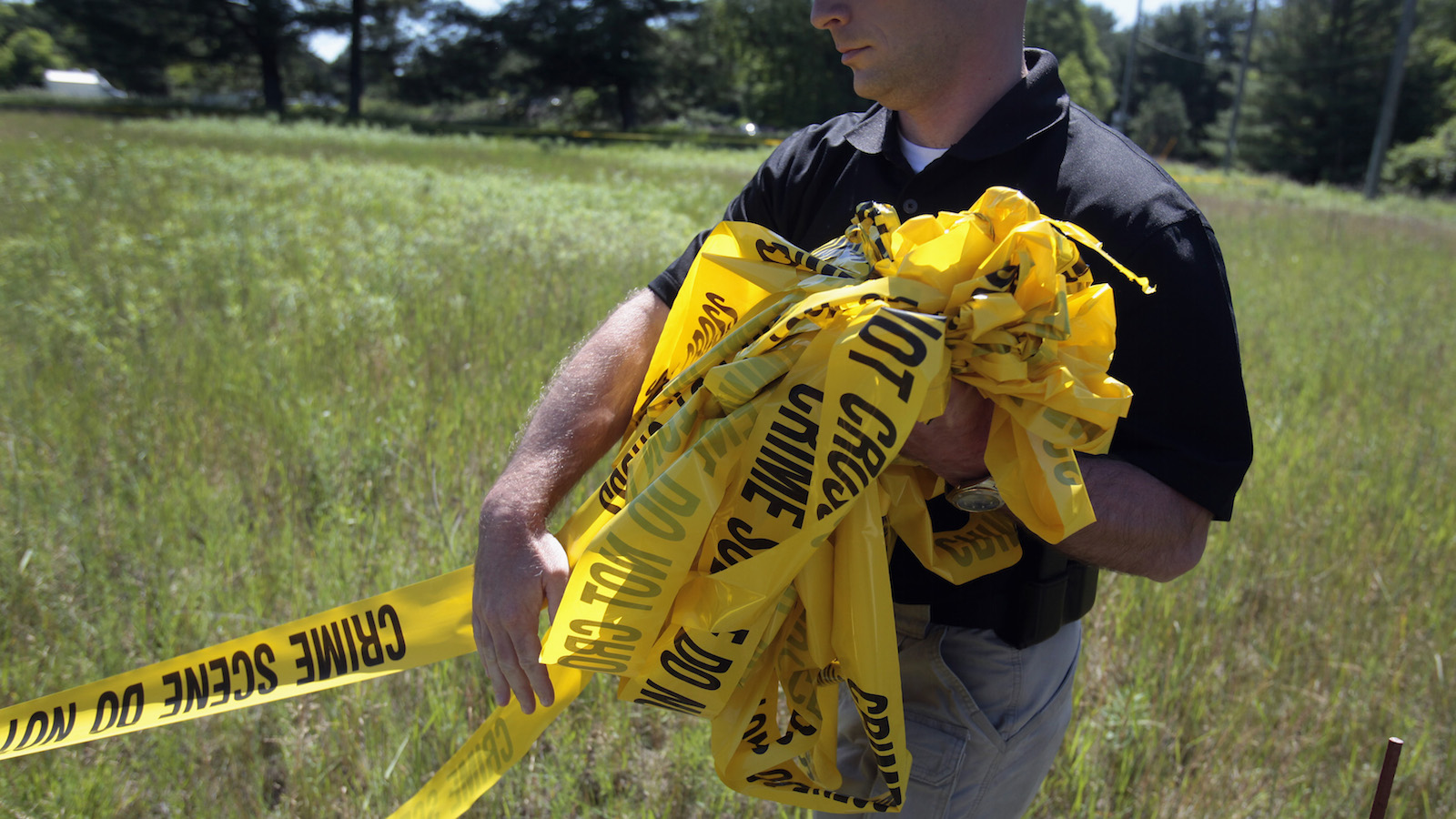 A federal investigator carries yellow crime tape at a field which investigators are prepared to dig up for the remains of former Teamsters boss Jimmy Hoffa in Oakland Township, Michigan June 17, 2013. The latest search for Hoffa, who disappeared in 1975 in what law enforcement officials believe might have been an organized crime hit, brought investigators on Monday to an overgrown vacant field in suburban Detroit.    REUTERS/ Rebecca Cook  (UNITED STATES - Tags: CRIME LAW) - RTX10R55