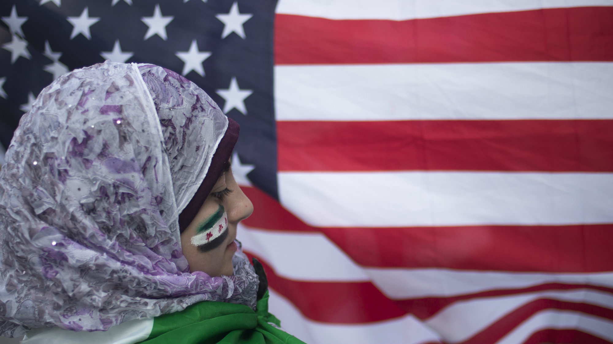 With cheeks painted in the colors of Syria's flag, 13-year-old displaced Syrian girl Malek Al Rifai stands in front of a U.S. flag while taking part in a protest in front of the United Nations building in New York August 21, 2013.