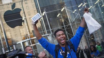 One of the first customers to purchase the Apple iPhone 5S celebrates after exiting the Apple Retail Store on Fifth Avenue in Manhattan, New York September 20, 2013