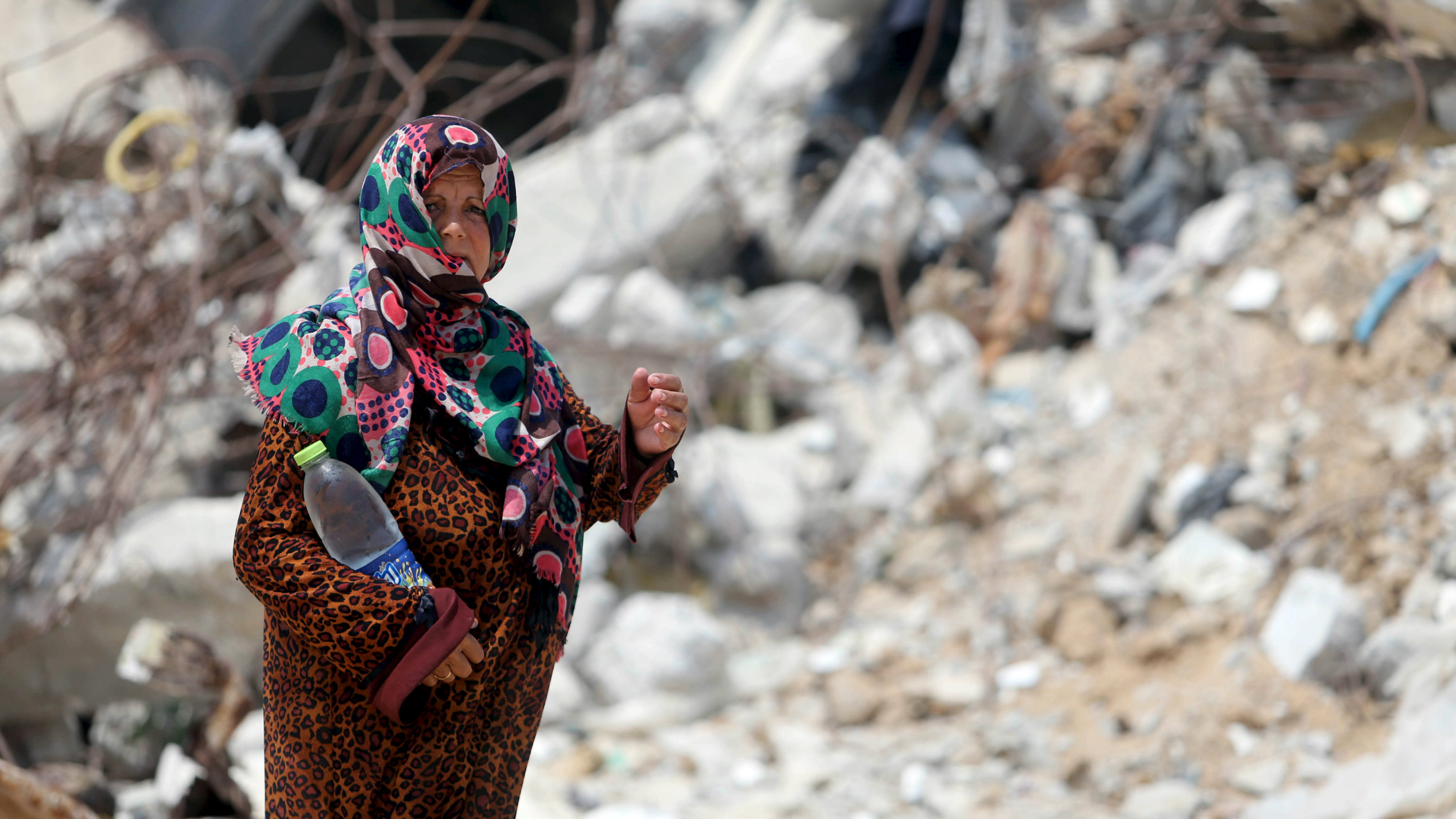 A Palestinian woman, whose house was destroyed by what witnesses said was Israeli shelling during a 50-day war last summer, holds a bottle as she walks outside her makeshift shelter during a wave of heat in Khan Younis in the southern Gaza Strip August 3, 2015.