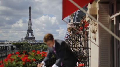 An employee prepares breakfast in front of the Eiffel tower at the Parisian luxury hotel Le Plaza Athenee, France July 30, 2015.