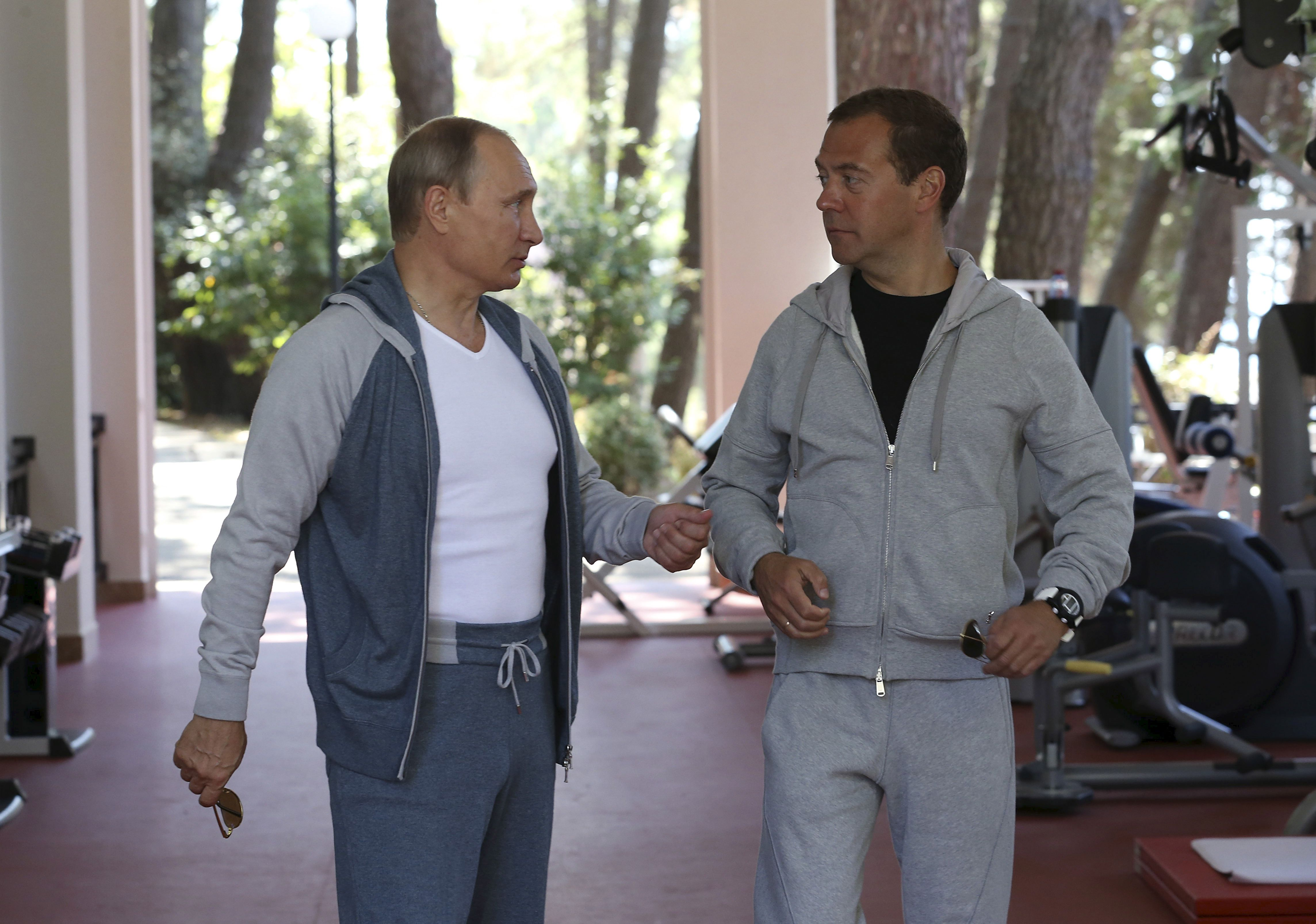 Russian President Vladimir Putin (L) talks with Prime Minister Dmitry Medvedev in a gym at the Bocharov Ruchei state residence in Sochi, Russia, August 30, 2015. REUTERS/Yekaterina Shtukina/RIA Novosti/Pool ATTENTION EDITORS - THIS IMAGE HAS BEEN SUPPLIED BY A THIRD PARTY. IT IS DISTRIBUTED, EXACTLY AS RECEIVED BY REUTERS, AS A SERVICE TO CLIENTS. - RTX1Q9I5