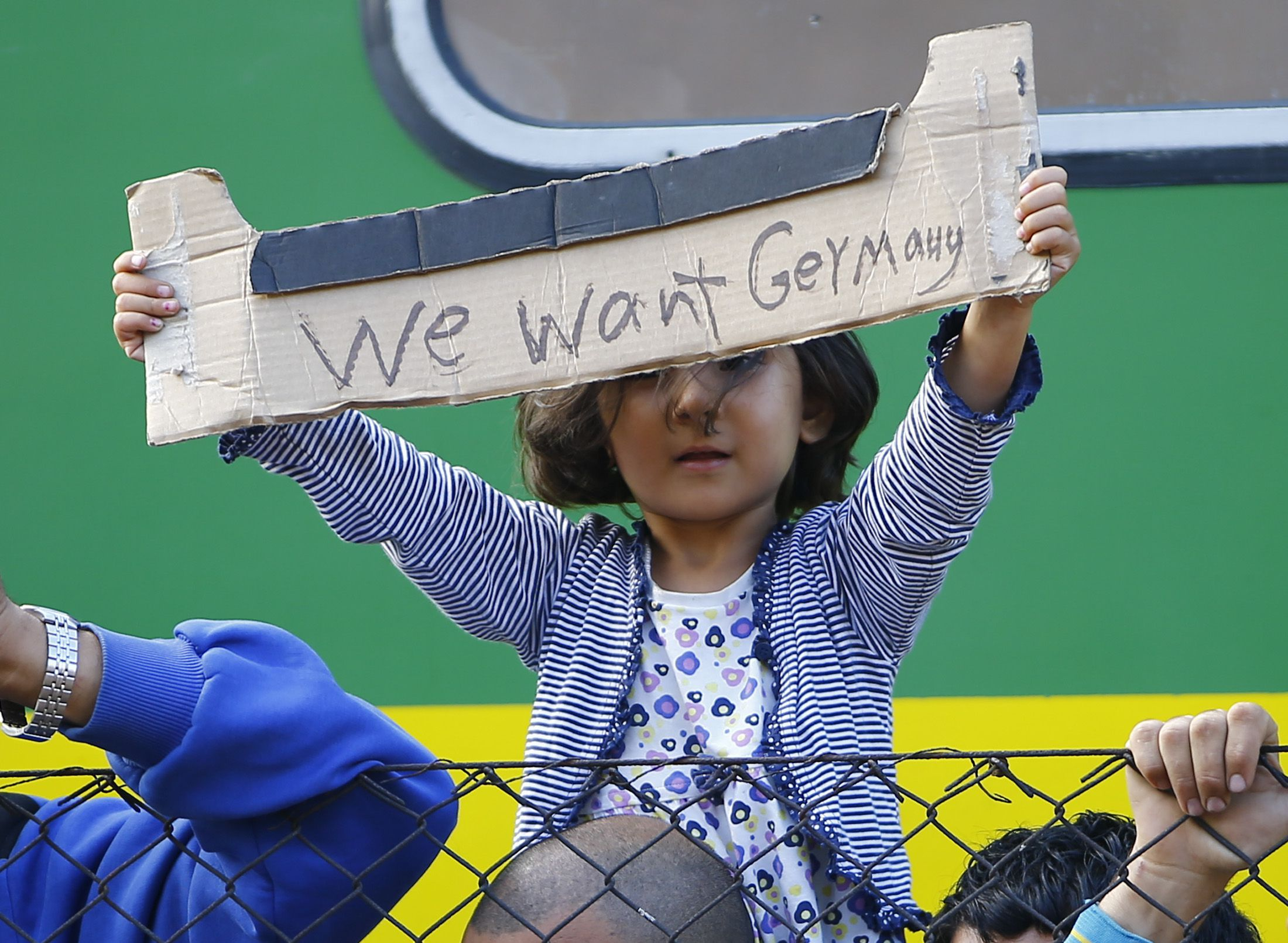 A young migrant girl holds up a sign during a protest in front of a train at Bicske railway station, Hungary, September 4, 2015.  Hundreds of migrants, many of them refugees from the Syrian war, woke after a night spent on a packed train stranded at a railway station west of Budapest, refusing to go to a nearby camp to process asylum seekers. The train had left Budapest on Thursday morning after a two-day standoff at the city's main railway station as police barred entry to some 2,000 migrants. Hungary says they must be registered, as per European Union rules, but many refuse, fearing they will be sent back to Hungary if caught later in western and northern Europe.  REUTERS/Leonhard Foeger TPX IMAGES OF THE DAY   - RTX1R1KW