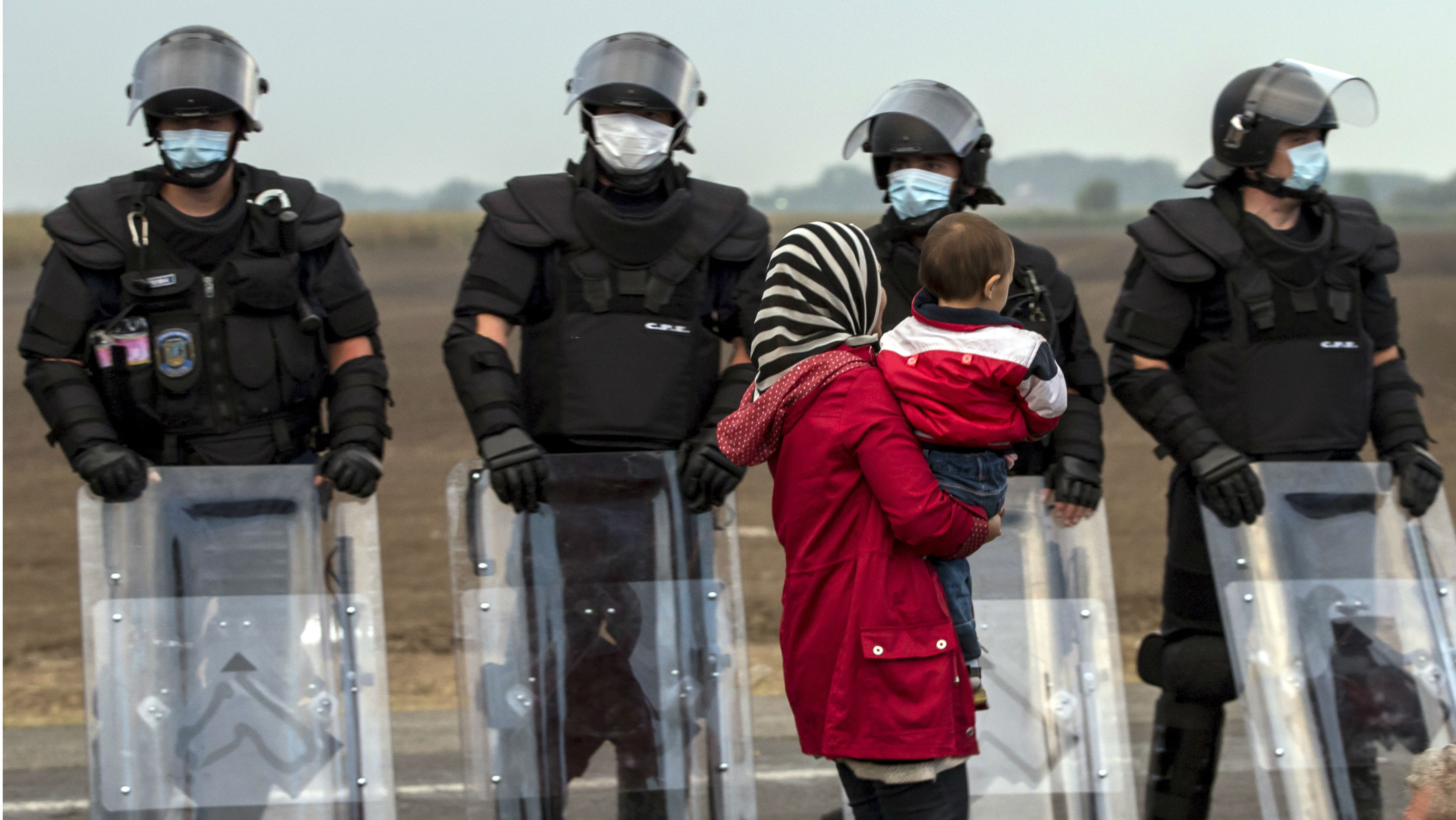 A migrant carries a child as she waits for a bus in front of riot police after crossing into Hungary from the border with Serbia on a field near the village of Roszke, September 5, 2015. Austria and Germany threw open their borders to thousands of exhausted migrants on Saturday, bussed to the Hungarian border by a right-wing government that had tried to stop them but was overwhelmed by the sheer numbers reaching Europe's frontiers. Left to walk the last yards into Austria, rain-soaked migrants, many of them refugees from Syria's civil war, were whisked by train and shuttle bus to Vienna, where many said they were resolved to continue on to Germany. REUTERS/Marko Djurica