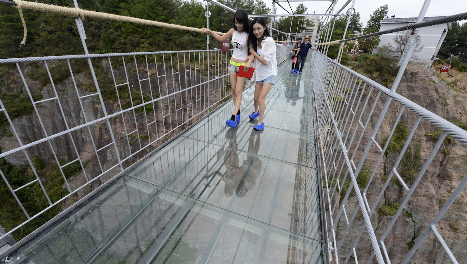 Tourists look down as they walk on a glass suspension bridge at the Shiniuzhai National Geo-park in Pinging county, Hunan province, China, September 24, 2015. The 300-metre-long (984 ft) glass bridge, which opened to tourists for the first time on Thursday, spans over a canyon which is about 180 metre deep (591 ft), local media reported. REUTERS/China Daily CHINA OUT. NO COMMERCIAL OR EDITORIAL SALES IN CHINA      TPX IMAGES OF THE DAY      - RTX1S6SS