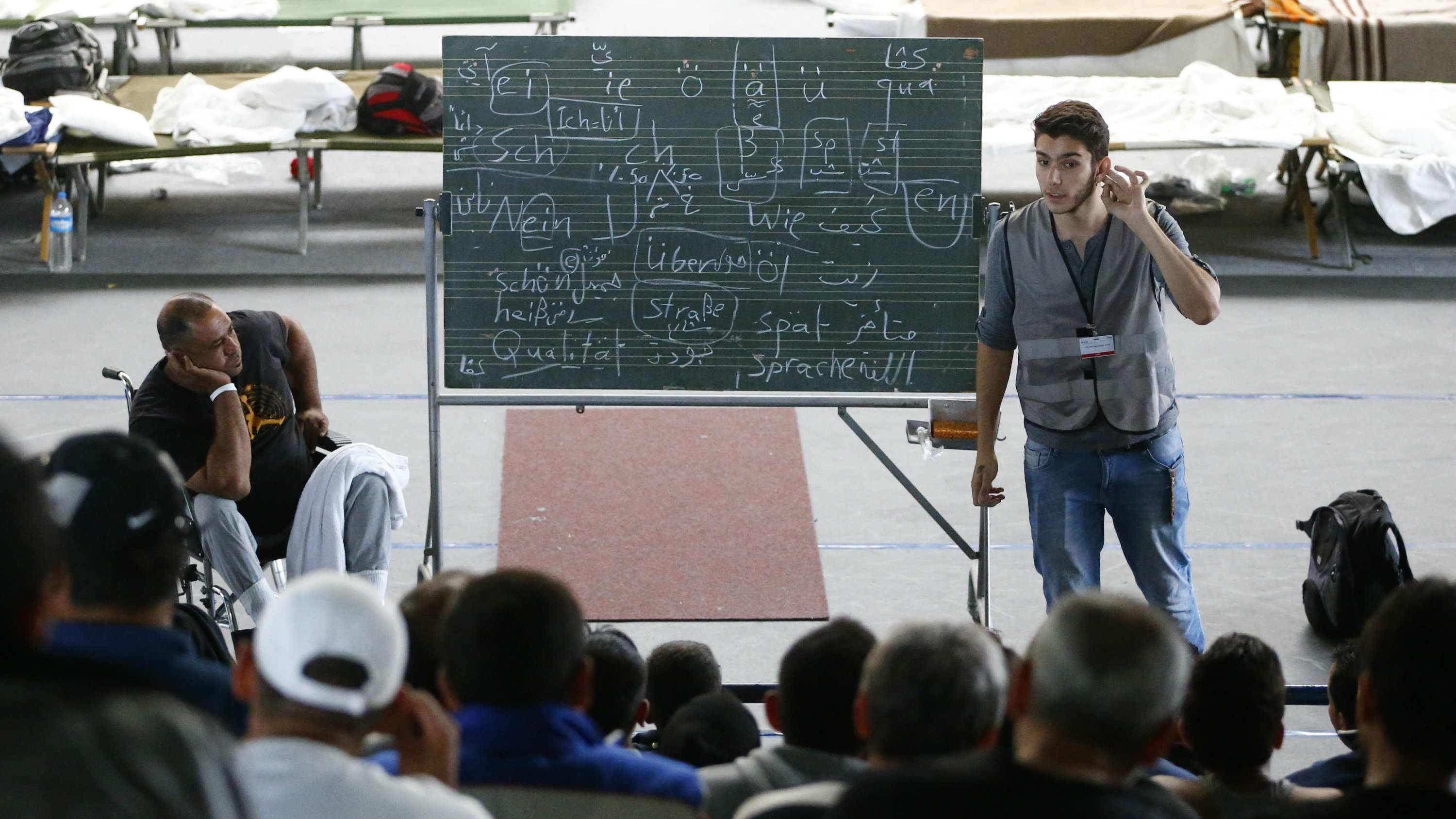 A volunteer conducts German language lessons for migrants inside an improvised shelter at a sports hall in Hanau, Germany, September 24, 2015.
