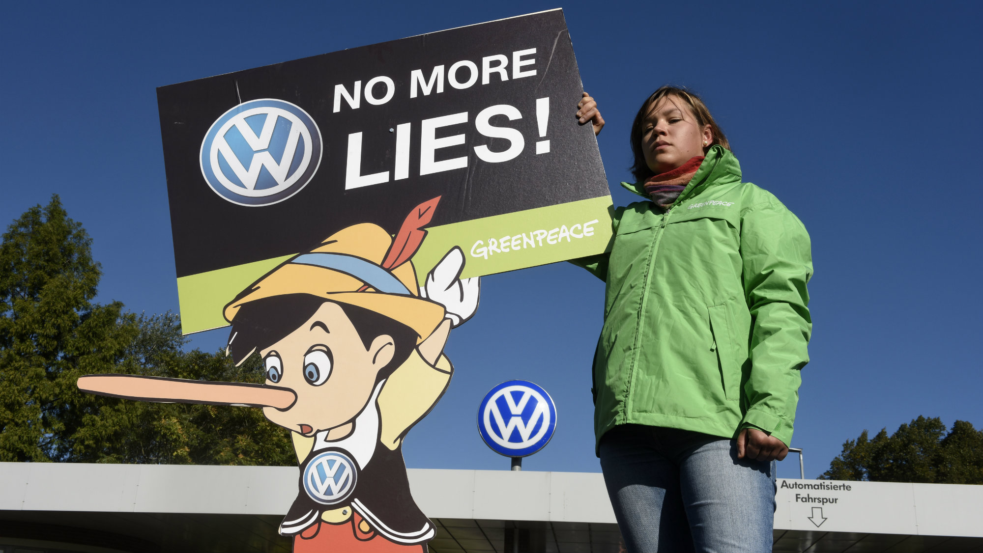 """A Greenpeace activist holds a banner during a protest in front of Volkswagen's """"Sandkamp"""" gate in Wolfsburg, Germany September 25, 2015."""