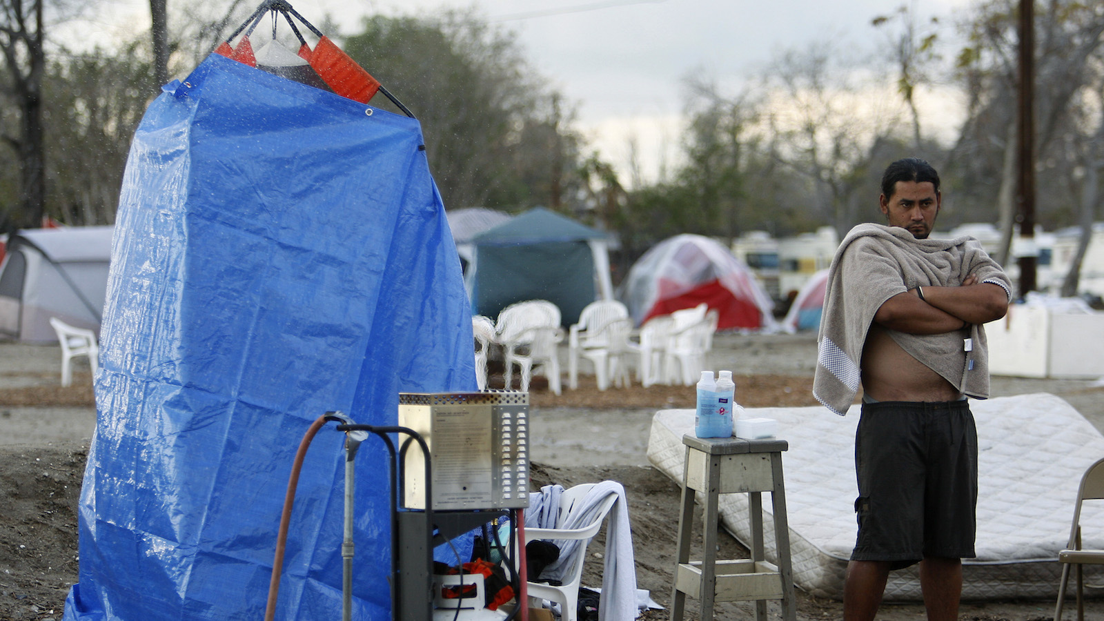 """A man waits to use the only shower for the hundreds of residents at """"tent city"""", a terminus for the homeless in Ontario, a suburb outside Los Angeles, California December 19, 2007. The noisy, dusty camp sprang up in July with 20 residents and now numbers 200 people, including several children, and is still growing as the region has been hit by the U.S. housing crisis. While no current residents claim to be victims of foreclosure, all agree that """"tent city"""" is a symptom of the wider economic downturn.  Picture taken December 19, 2007.  TO MATCH FEATURE USA-HOUSING/SOCIAL   REUTERS/Lucy Nicholson (UNITED STATES) - RTX4X66"""