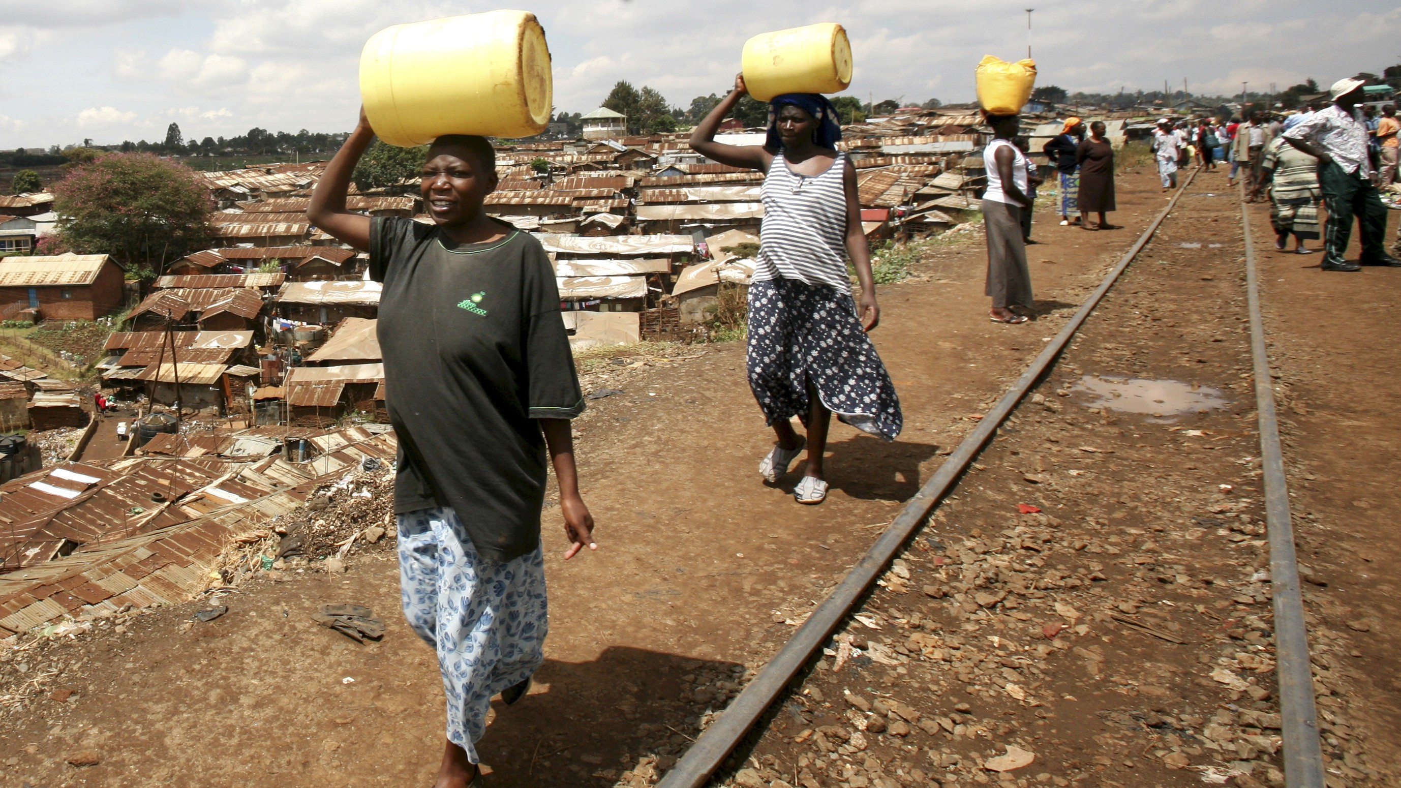 Women carry jerry-cans of water on their heads as they walk to Kibera slums in Kenya's capital Nairobi.