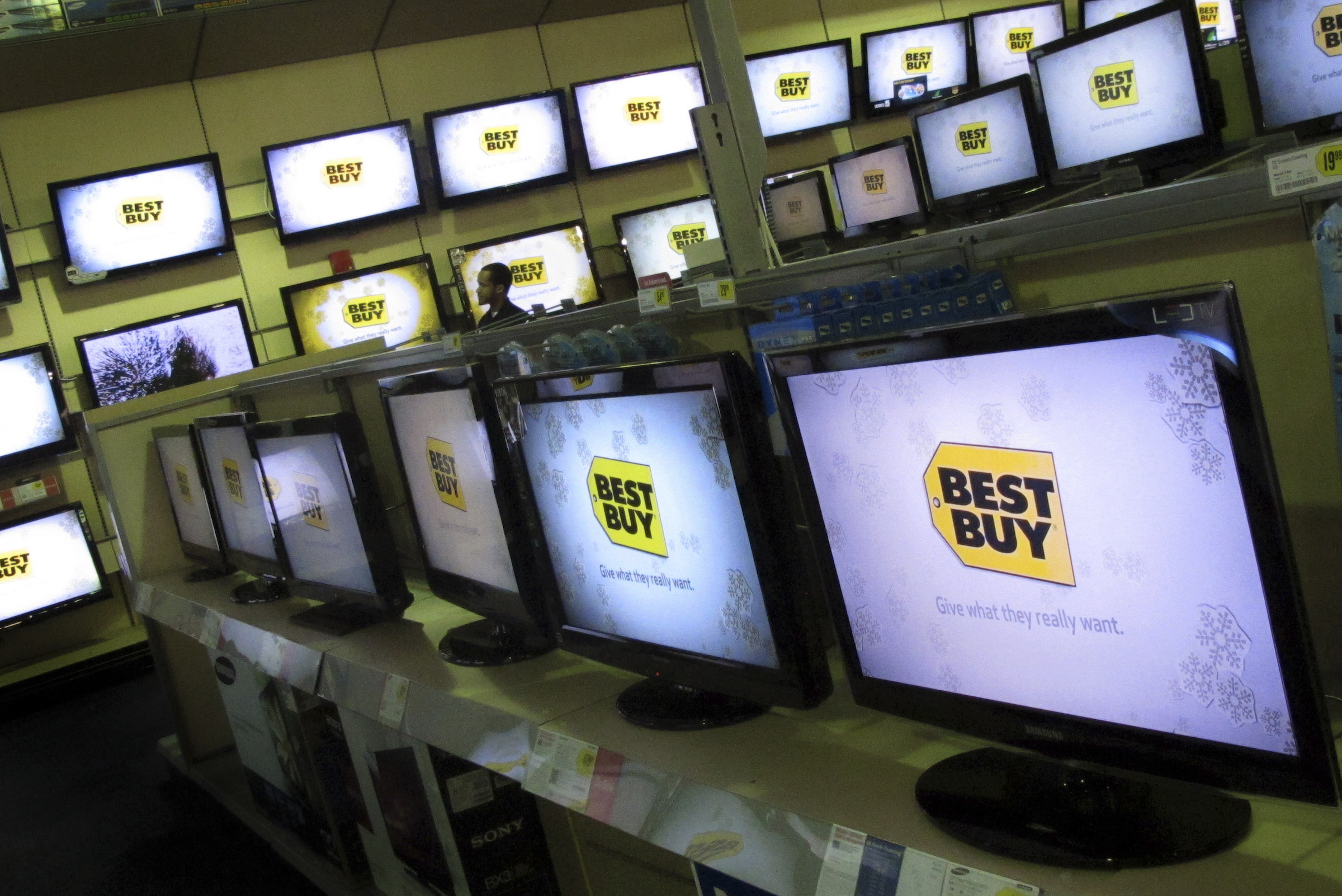 A man walks past televisions for sale at a Best Buy store in New York November 23, 2010. REUTERS/Mike Segar (UNITED STATES - Tags: BUSINESS)