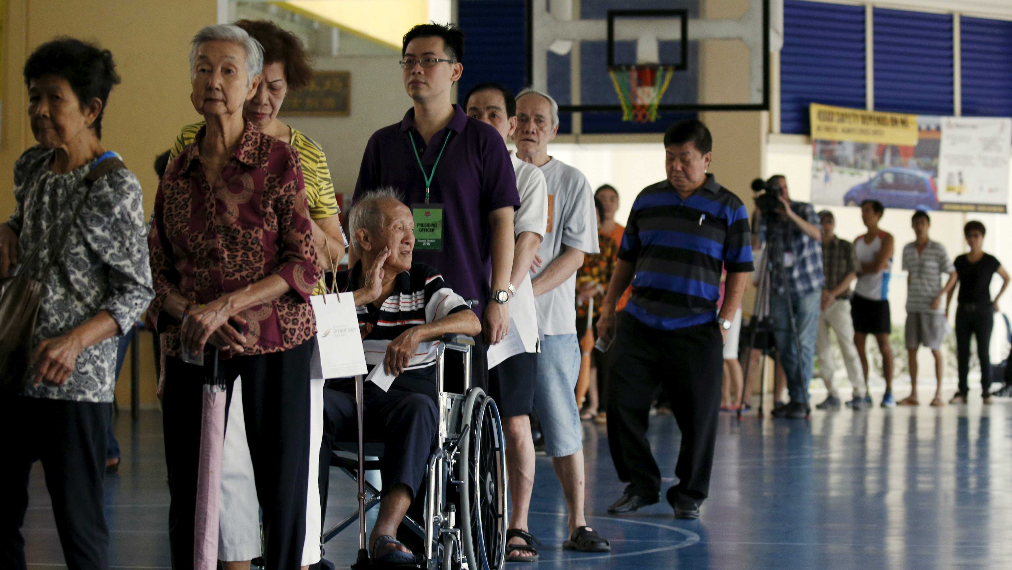 Voters queue to cast their ballots during the general election at a polling center in Singapore September 11, 2015