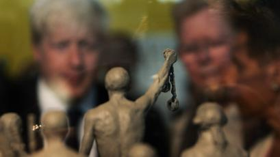 Mayor of London Boris Johnson, left, looks at a model of a statue to be built as a permanent slavery memorial at City Hall in London.