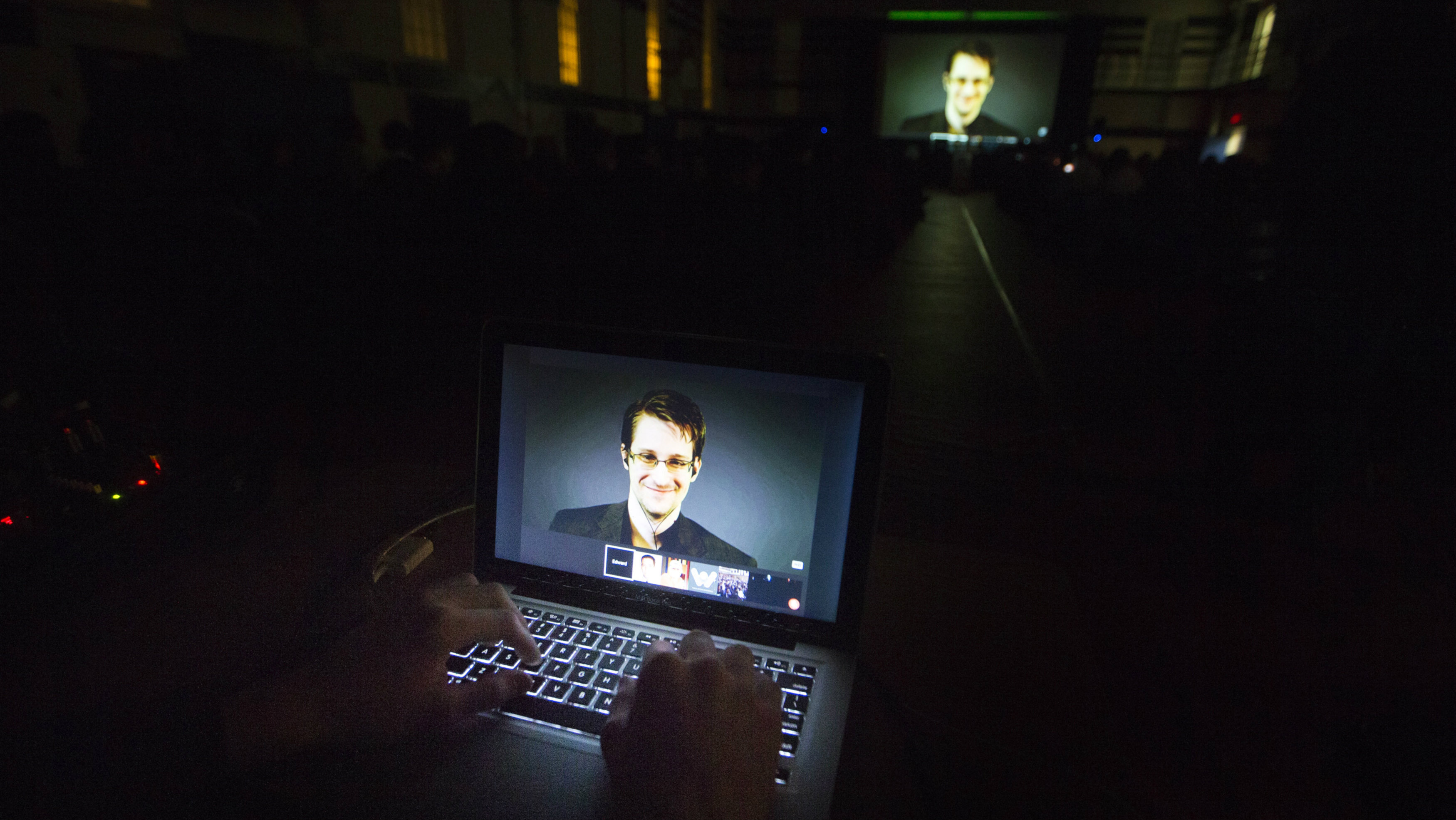 A student works on a computer that is projecting former U.S. National Security Agency contractor Edward Snowden as he appears live via video.