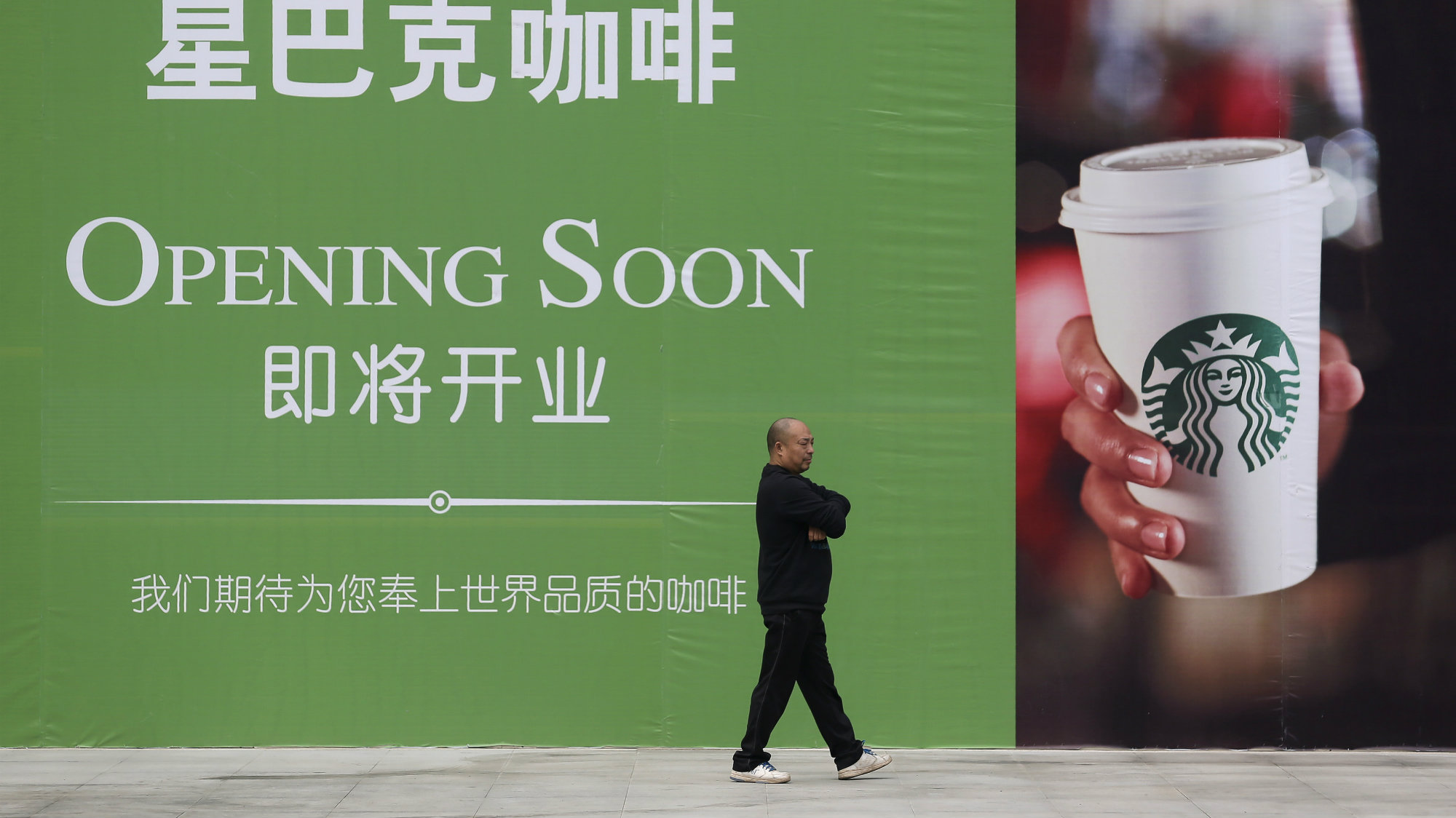 A man walks past a forthcoming Starbucks billboard in Wuhan, China.