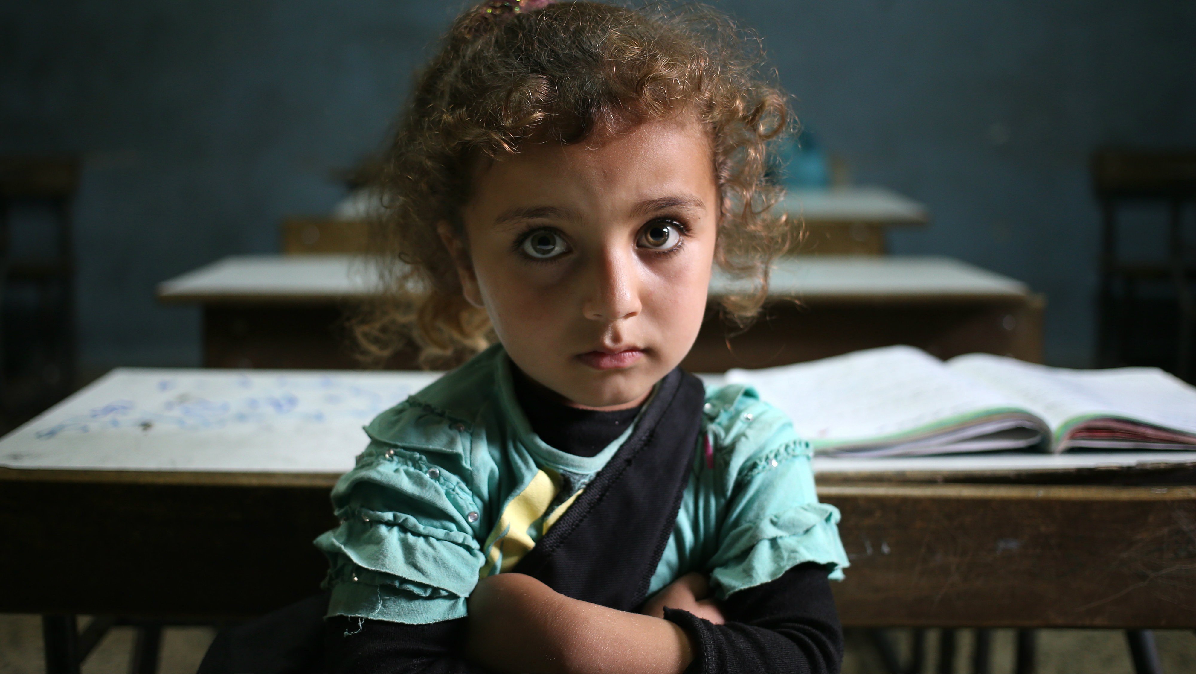 In this Thursday, May 29, 2014 file photo, a Syrian refugee girl sits in a classroom at a Lebanese public school where only Syrian students attend classes in the afternoon, at Kaitaa village in north Lebanon. Forty percent of children from five conflict-scarred Middle Eastern countries are not in school, the U.N. child welfare agency said in a report Thursday, Sept. 3, 2015, warning of a lost generation and a dim future for the region. UNICEF said 13.7 million out of 34 million school age children in Syria, Iraq, Yemen, Libya and Sudan are not getting an education, almost double the number five years ago. (AP Photo/Hussein Malla, File)