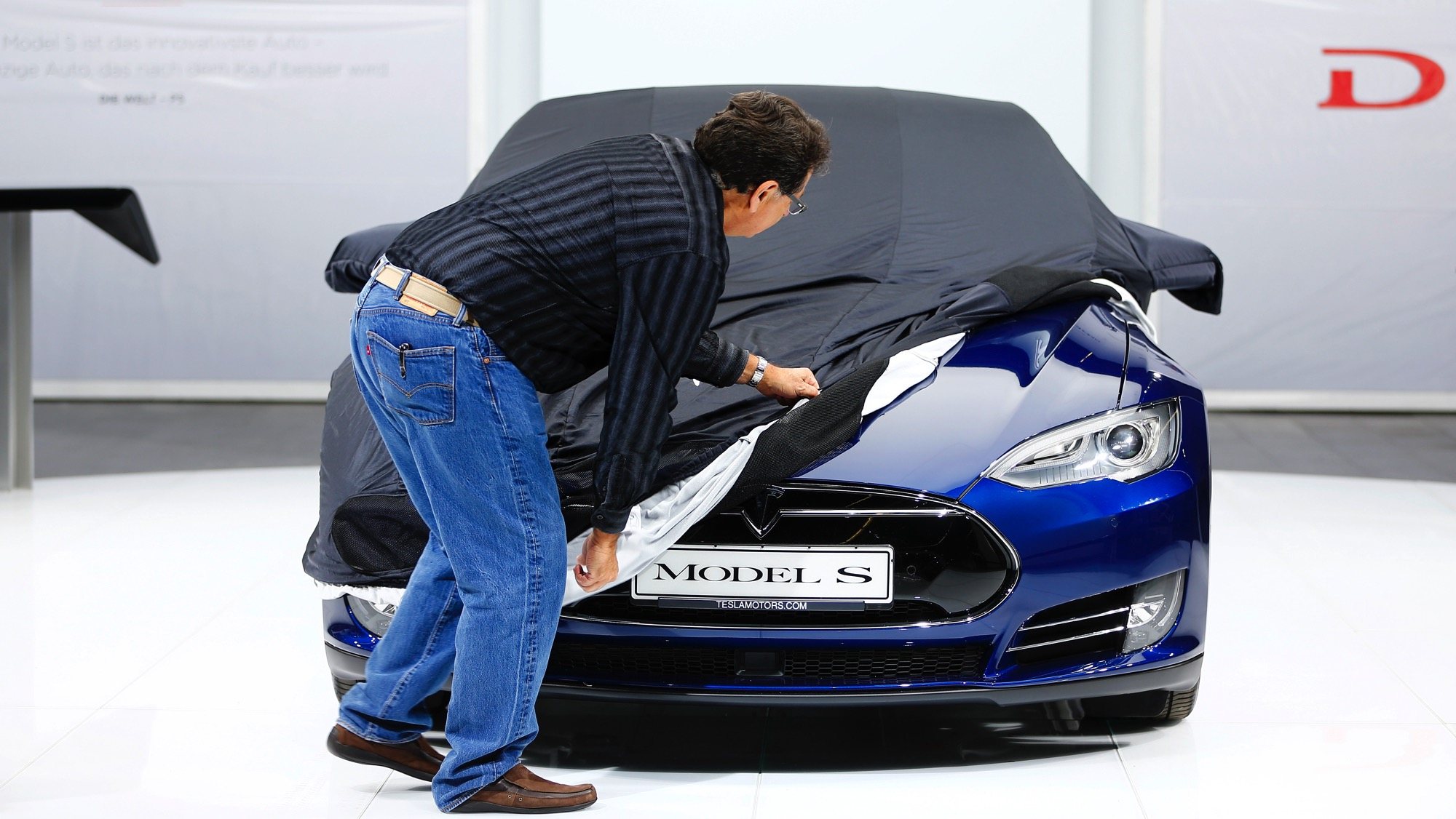 An employee covers a Tesla Model S car during the media day at the Frankfurt Motor Show (IAA) in Frankfurt