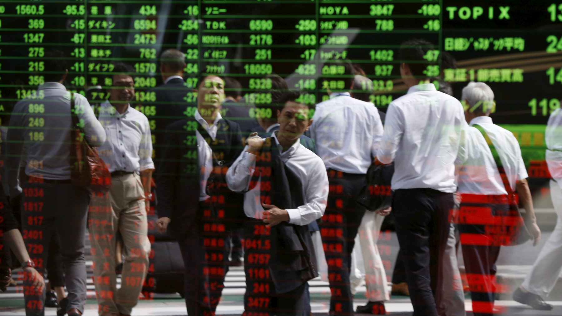 Passersby are reflected on a stock quotation board at a brokerage in Tokyo, Japan, September 29, 2015. Asian shares skidded to 3-1/2-year lows and the dollar sagged on Tuesday, pulled down by a sharp losses on Wall Street after weak Chinese data rekindled worries about its fragile economy. REUTERS/Issei Kato TPX IMAGES OF THE DAY