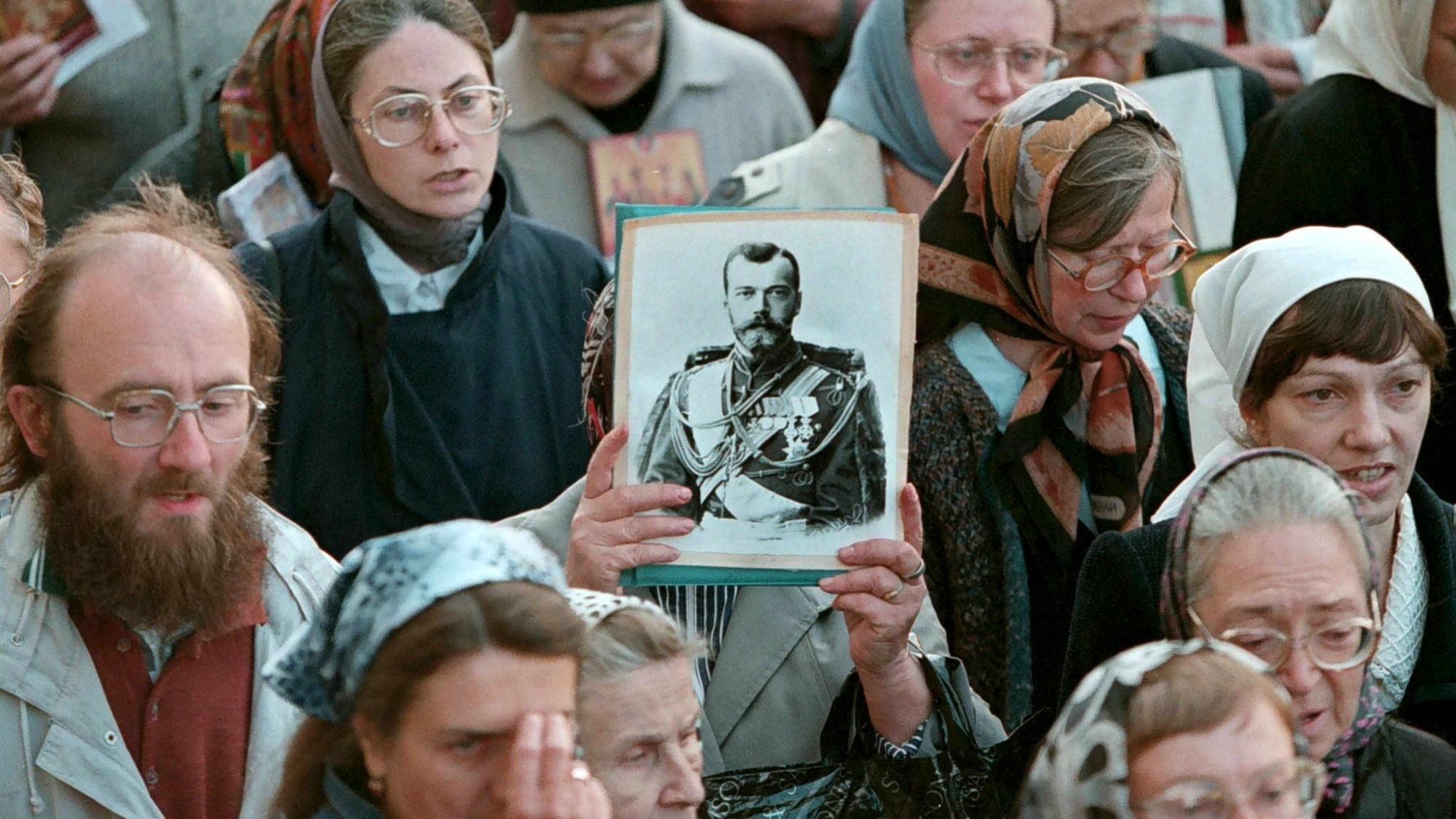 Russian orthodox believers pray and hold a portrait of the last Russian tsar Nicholas II during a religious procession marking a canonization of him by Russian Orthodox church, in downtown St.Petersburg 24 August 2000. Tsar Nicholas and his family, who perished in 1918 at the hands of the Bolsheviks during the Russian revolution, were canonised on 20 August 2000.