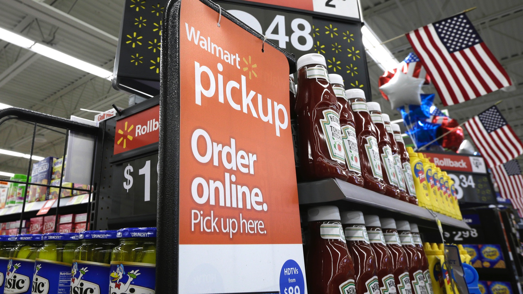 A sign encouraging customers to order grocery items online and pick them up at a store is displayed at a Wal-Mart Neighborhood Market in Bentonville, Ark., Thursday, June 4, 2015. (AP Photo/Danny Johnston)