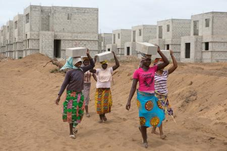 Women carry bricks at the construction site of real estate company Sipim in Grand Bassam, Ivory Coast. They are paid 25 West African francs (about $0.04) for each brick.