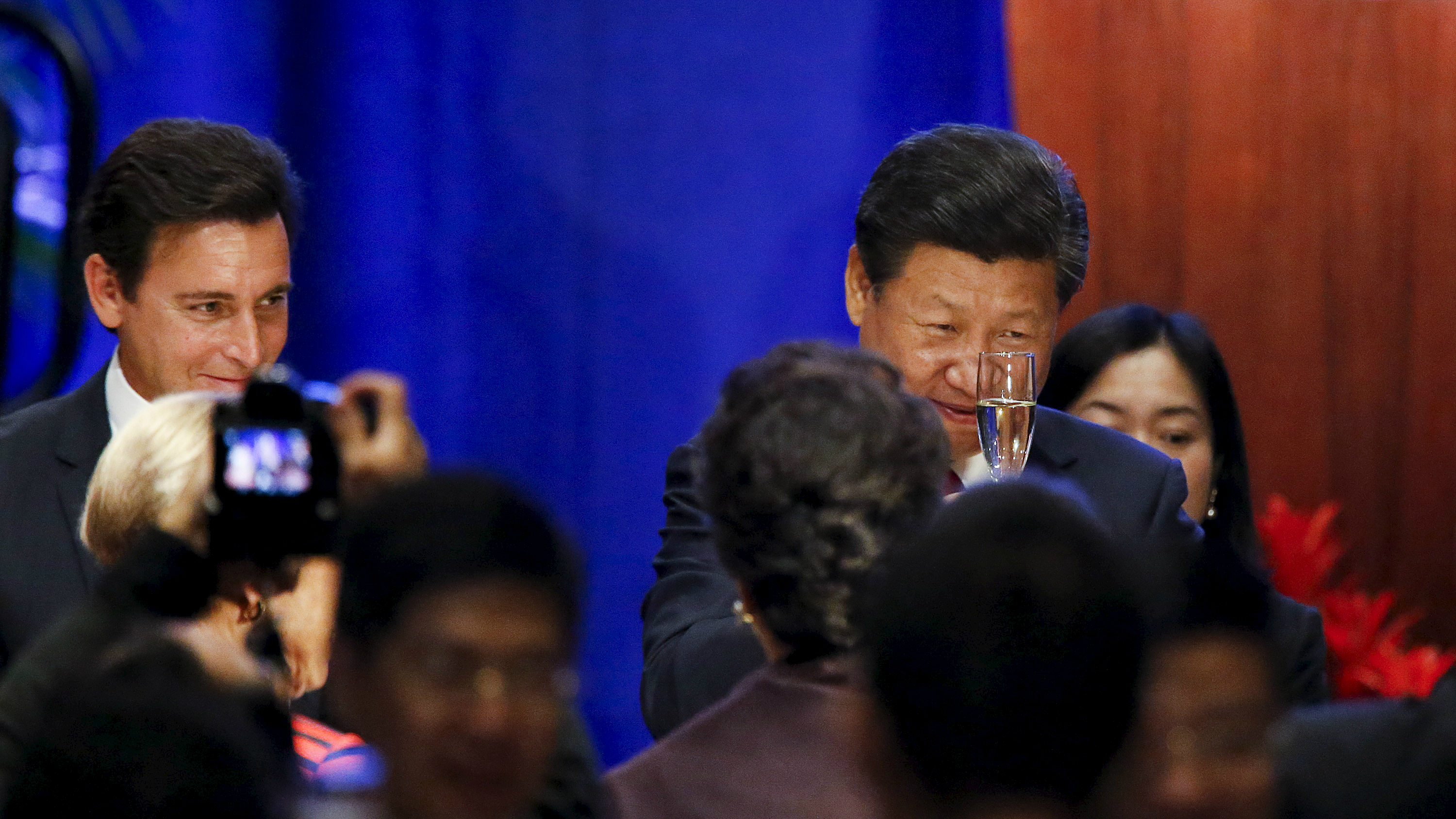 Chinese President Xi Jinping (R) raises his glass during a toast as Mark Fields (L), President and Chief Executive Officer of Ford Motor Company, looks on during a dinner reception in Seattle, Washington September 22, 2015.