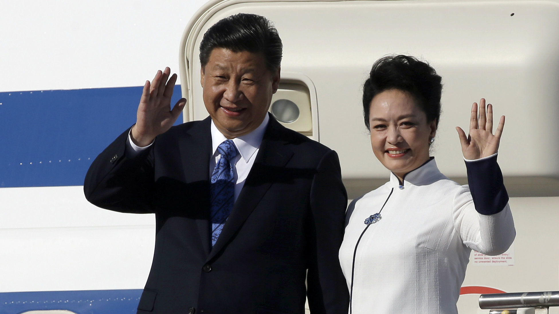 Chinese President Xi Jinping, left, and his wife Peng Liyuan wave upon arrival Tuesday, Sept. 22, 2015, at Boeing Field in Everett, Wash. Xi is spending three days in Seattle before traveling to Washington, D.C., for a White House state dinner on Friday. (AP Photo/Elaine Thompson)
