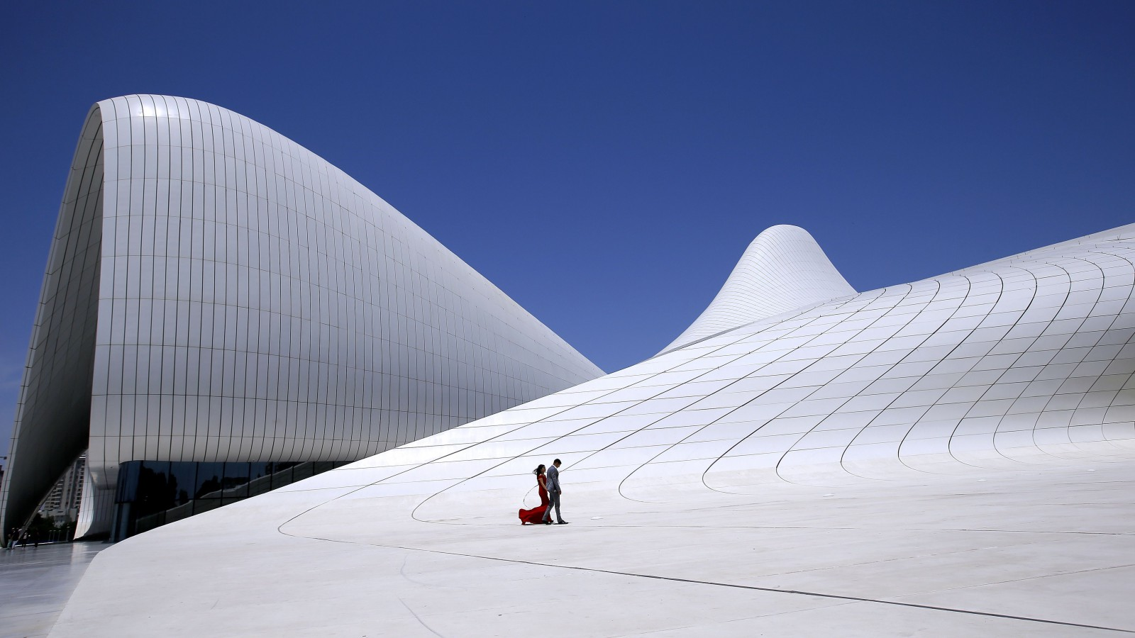 epa04806370 Newly-weds pose for their wedding photographer (not in pictured) in front of the Heydar Aliyev Center in downtown of Baku, Azerbaijan, 18 June 2015. The building was designed by Iraqi-British architect Zaha Hadid, over an area of 101801.0 square meters and was finished in 2014, becoming one of the modern symbols of Baku.  EPA/ROBERT GHEMENT