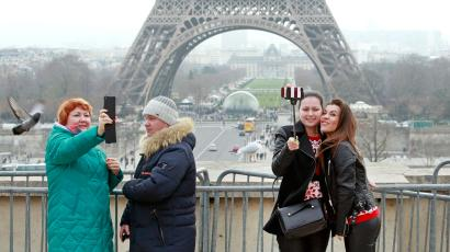 Tourists use a selfie stick on the Trocadero Square, with the Eiffel Tower in background, in Paris, Tuesday, Jan. 6, 2015. Selfie sticks have become enormously popular among tourists because you don't have to ask strangers to take your picture, and unlike hand-held selfies, you can capture a wider view without showing your arm. But some people find selfie sticks obnoxious, arguing that they detract from the travel experience. (AP Photo/Remy de la Mauviniere)