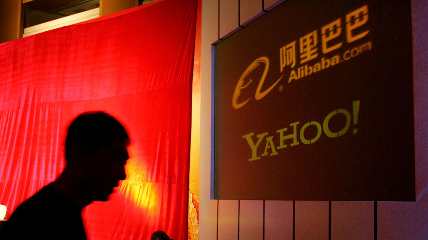 A Chinese man walks past a screen showing the Yahoo and Ali Baba.com logos moments before an Ali Baba and Yahoo joint press conference at the China World hotel in Beijing Thursday, Aug. 11, 2005. Yahoo Inc. announced Thursday it would pay US$1 billion (euro810 million) in cash to acquire a 40 percent stake in the Chinese e-commerce firm Alibaba.com. The agreement makes Yahoo the largest strategic investor in Alibaba, and is the biggest deal yet in a flurry of investments in China by foreign Internet companies eager for a share of a market with more than 100 million people online. (AP Photo/Elizabeth Dalziel)