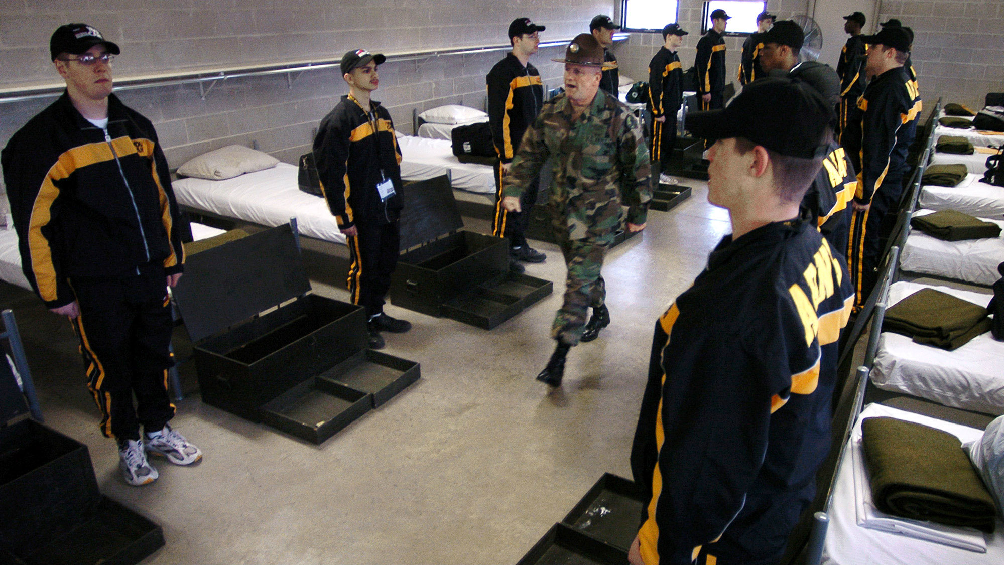 Sgt. James Locke, center, inspects recruits as they stand at attention in the concrete barracks Saturday, April 3, 2004, at the Army National Guard complex in Marseilles, Ill.