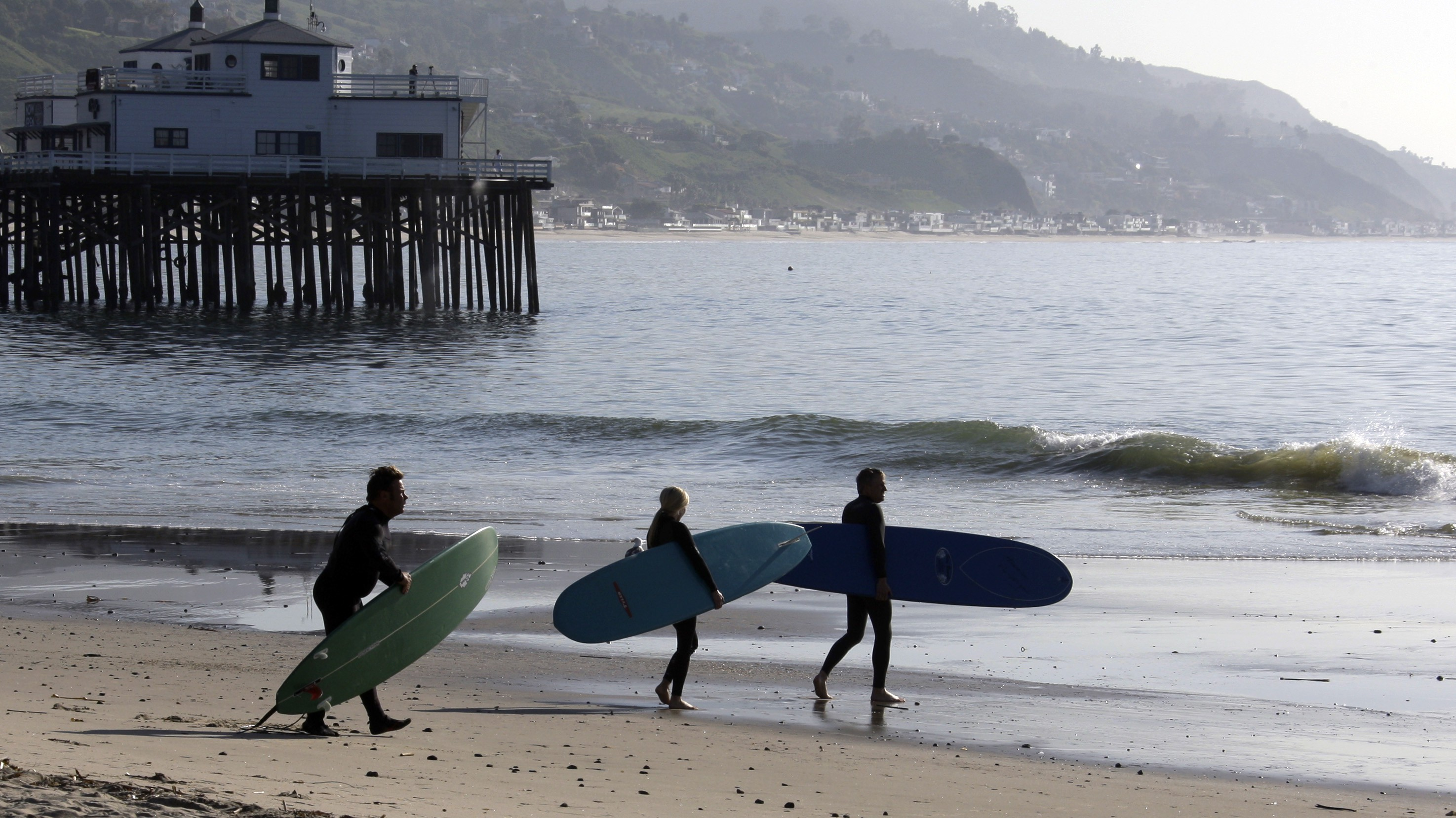 Surfers head for the waves at about the time the effects of a tsunami were expected, at Surfrider Beach in Malibu, Calif., Friday, March 11, 2011.
