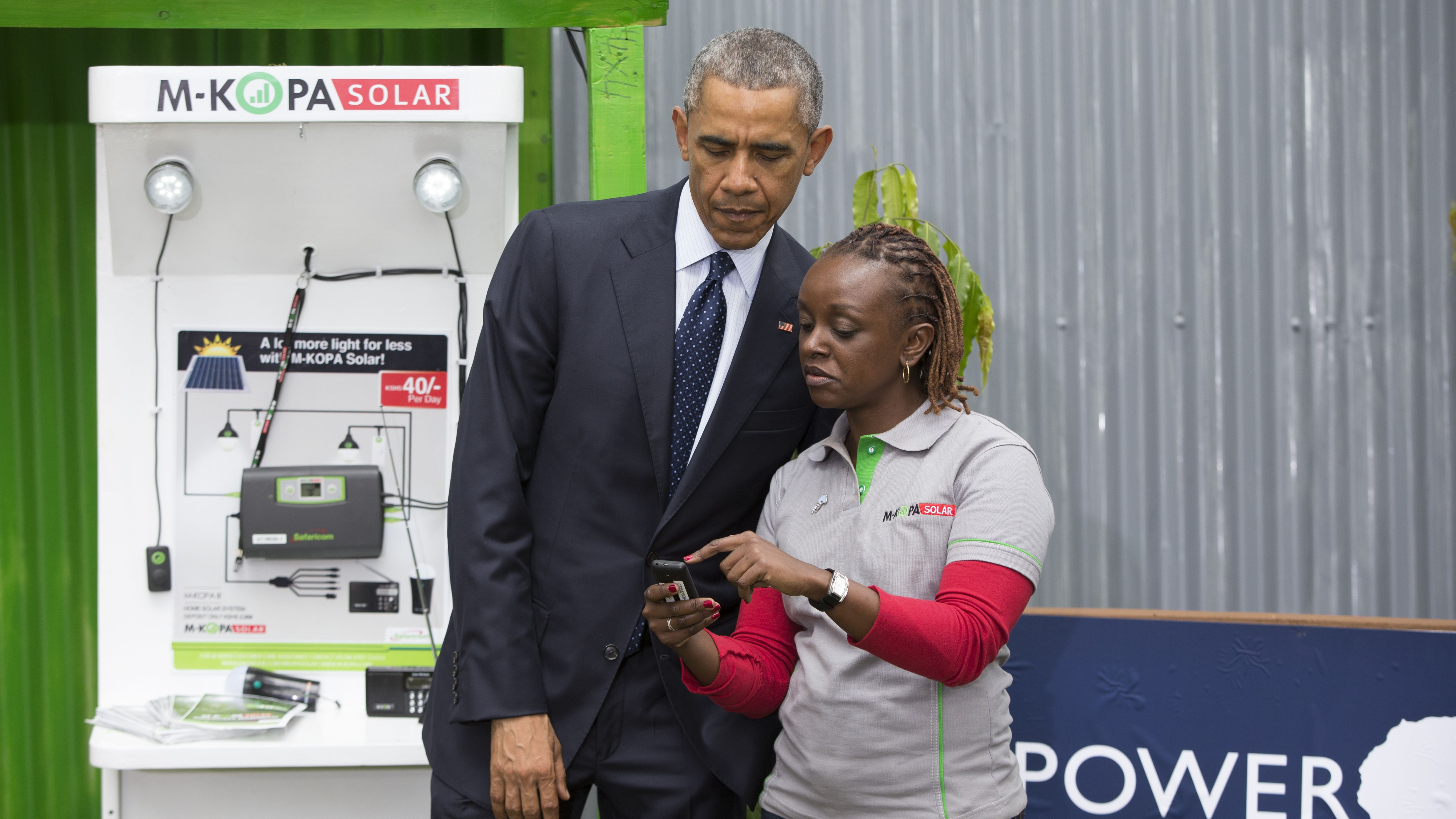 Barack Obama looks at an M-KOPA mobile payment platform and solar exhibit in Nairobi.