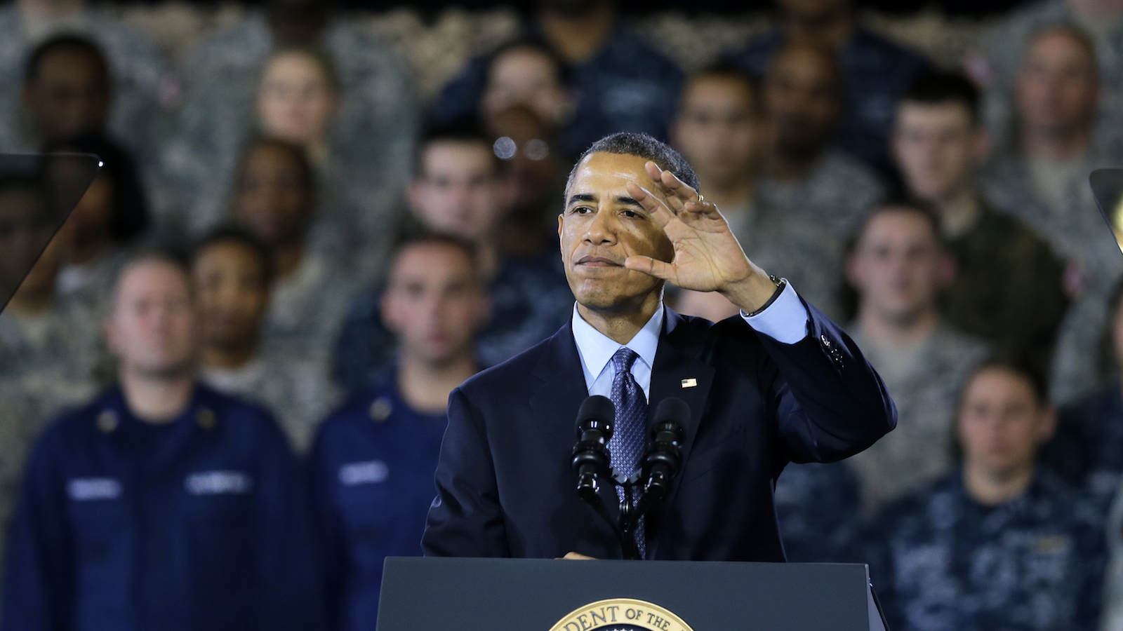President Barack Obama waves as he finishes speaking to military members and families Monday, Dec. 15, 2014, at Joint Base McGuire-Dix-Lakehurst, in Wrightstown, N.J. President Barack Obama said every American who has served in Afghanistan should be proud of what they've accomplished.  Obama is observing the end of combat operations in Afghanistan by visiting U.S. troops at New Jersey's Joint Base McGuire-Dix-Lakehurst. The base has been a launching point for deployments to Afghanistan. (AP Photo/Mel Evans)