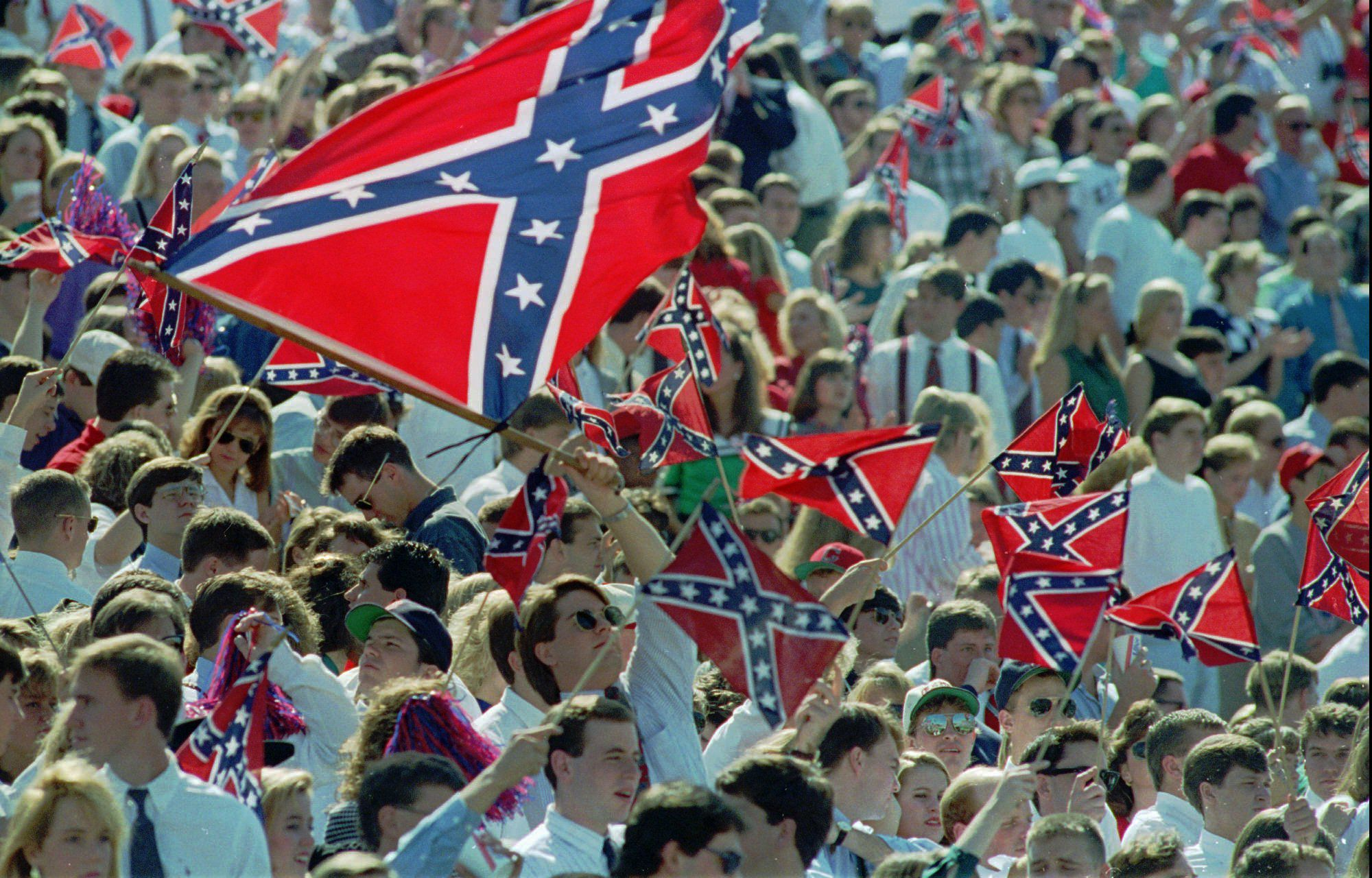 """Although the University of Mississippi has been disassociated for about 14 years from the """"Rebel"""" flag, shown being waved at an undated 1995 football game at the Oxford, Miss., institution, the school is concerned that discussions of past and present symbols such as the flag, the mascot Colonel Rebel and the fight song """"Dixie"""", will over shadow its current mission of developing a positive academic image. (AP Photo/Tannen Maury)"""
