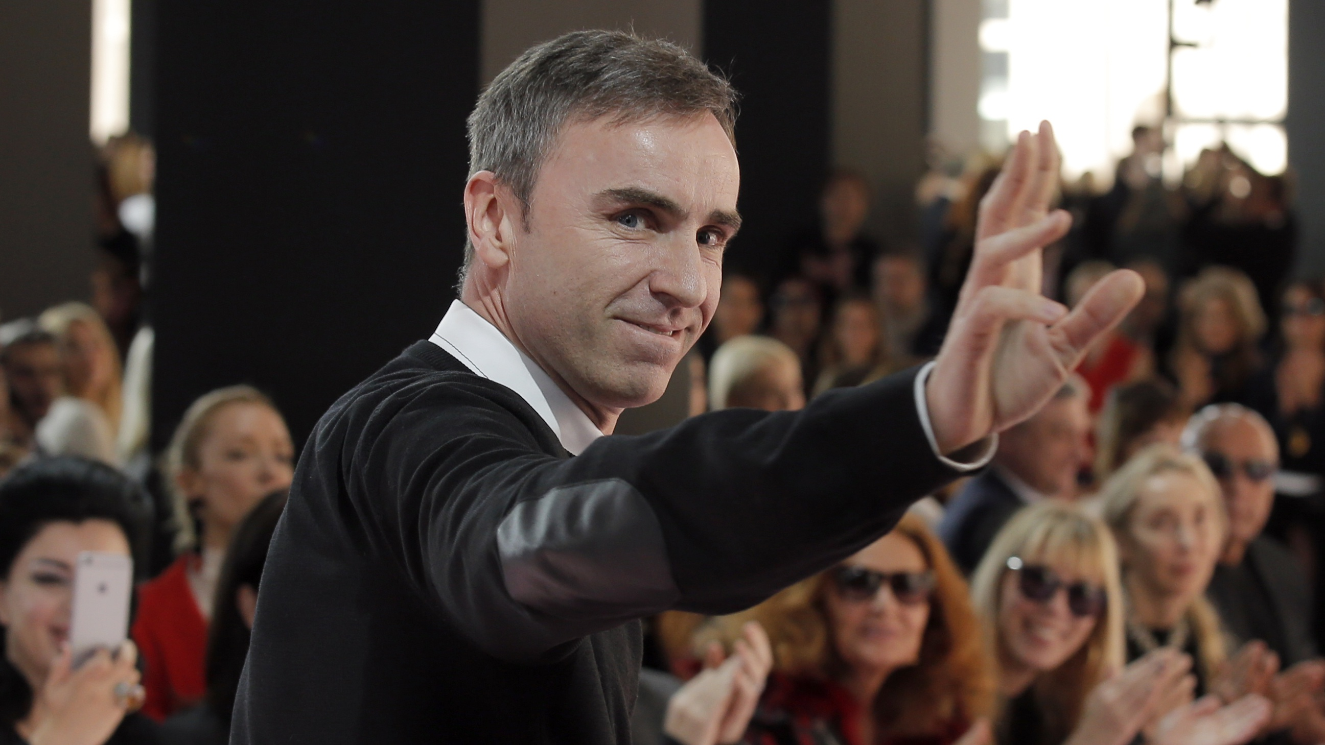 Belgian designer Raf Simons waves as he receives applause at the end of Christian Dior's ready to wear fall-winter 2015-2016 fashion collection, as part of Paris Fashion week, presented in Paris, France, Friday, March 6, 2015.