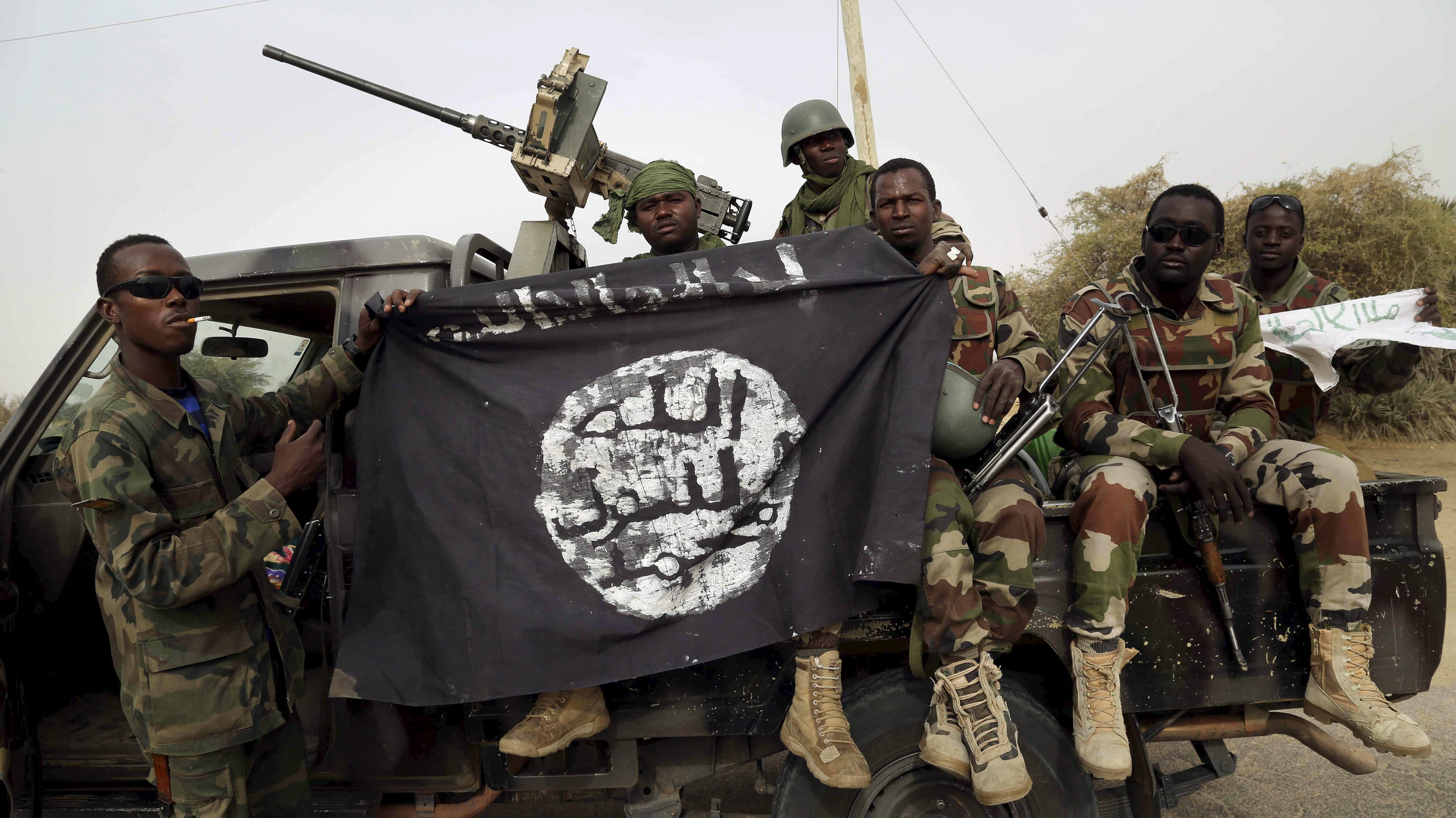 Nigerian soldiers hold up a Boko Haram flag that they had seized in the recently retaken town of Damasak, Nigeria, March 18, 2015. Chadian and Nigerien soldiers took the town from Boko Haram militants earlier this week. The Nigerian army said on Tuesday it had repelled Boko Haram from all but three local government districts in the northeast, claiming victory for its offensive against the Islamist insurgents less than two weeks before a presidential election. Picture taken March 18. REUTERS/Emmanuel Braun