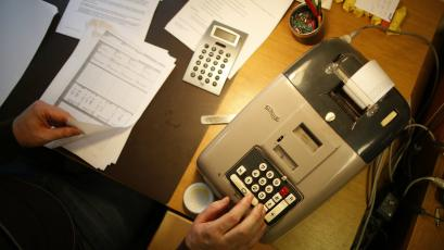 A German banker works with an old adding machine.