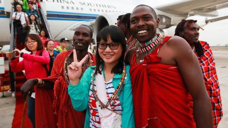 A Chinese tourist poses with traditional Kenyan Masaai dancers upon her arrival with a China Southern Airline plane at Jomo Kenyatta International Airport in Nairobi.